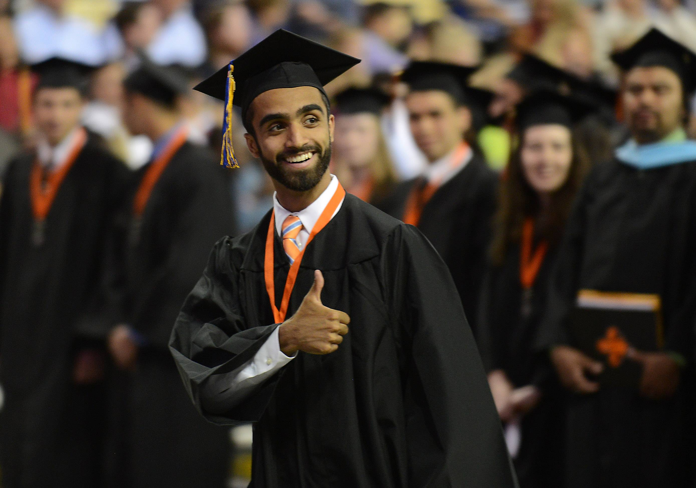 Farooq Chaudhry gives a thumbs up to people in the crowd as he takes his seat on the stage before St. Charles East's graduation ceremony at the Sears Centre in Hoffman Estates Sunday. He was one of the student speakers.