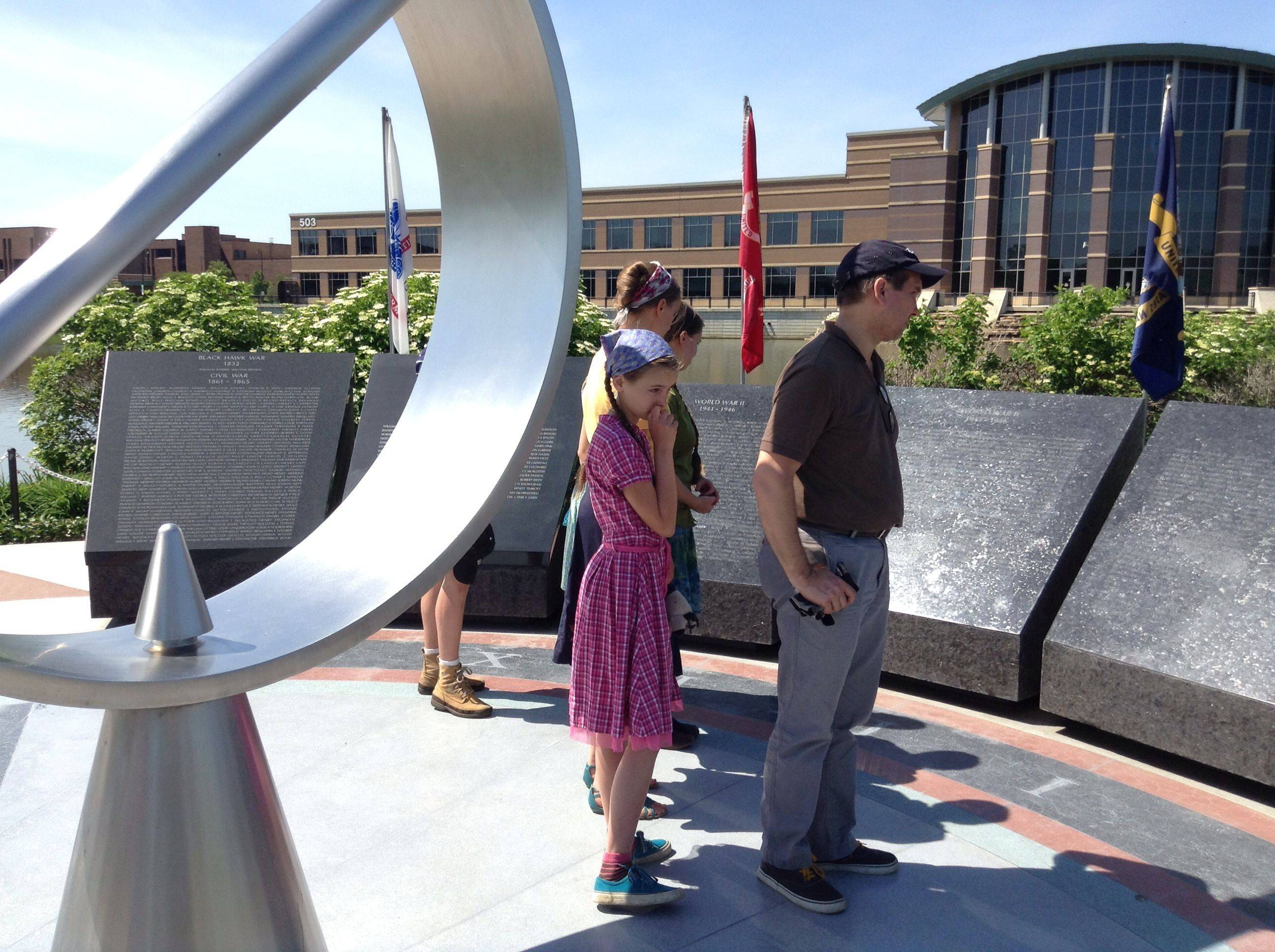Visitors to the DuPage County Veterans' Memorial study the names of residents who were killed in World War II. Roughly 60 people attended a Memorial Day observance on Sunday at the memorial in Wheaton.