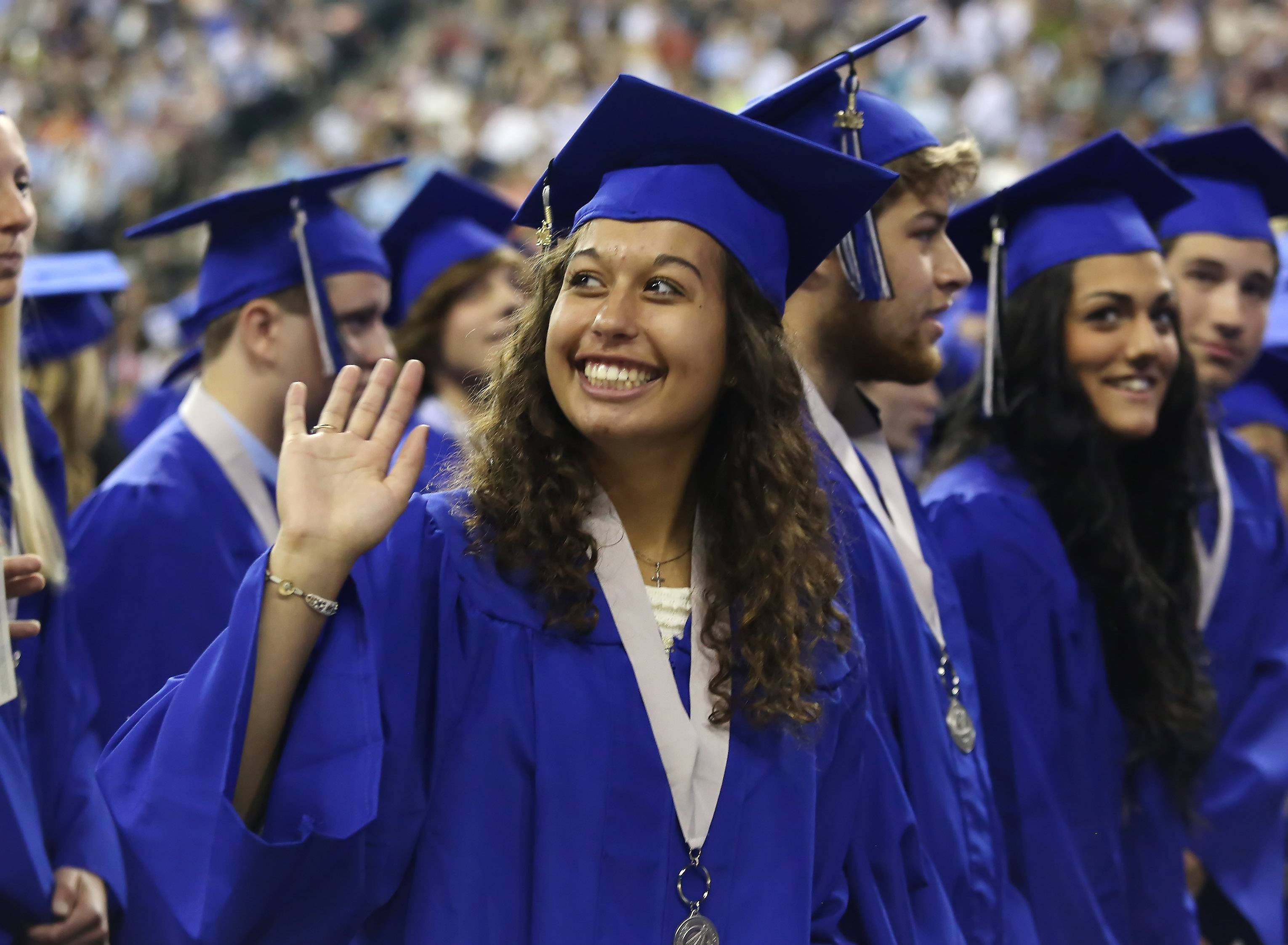 Victoria Parrilli waves to family during the St. Charles North High School graduation Sunday at the Sears Centre in Hoffman Estates. Family and friends watched as 505 students received their diplomas during the commencement exercises.