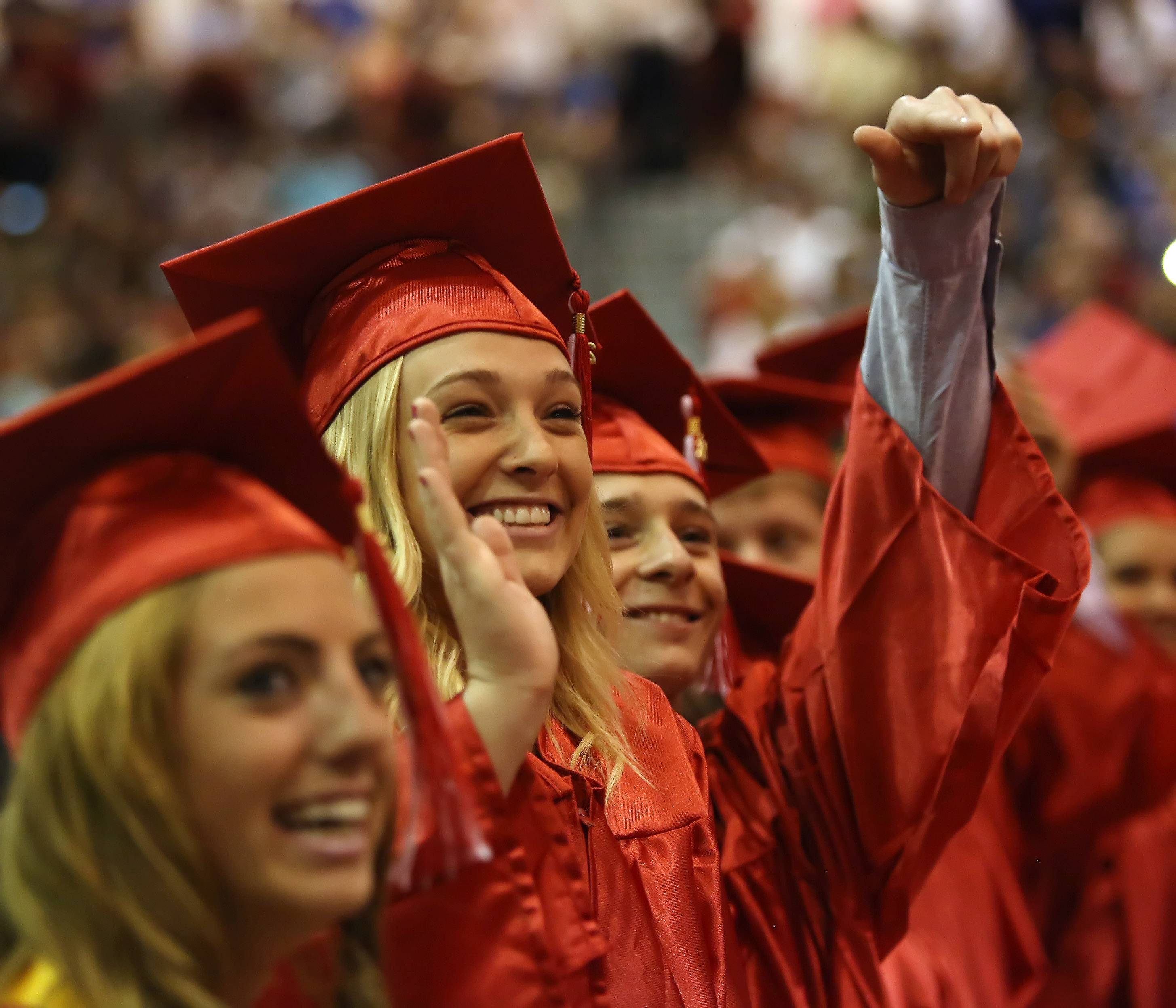 Kelly Wolski, left, and Kevin Woolums wave to family during the Grant Community High School graduation Sunday in the field house at the Fox Lake school. Family and friends watched as 399 seniors received their diplomas during the commencement exercises.