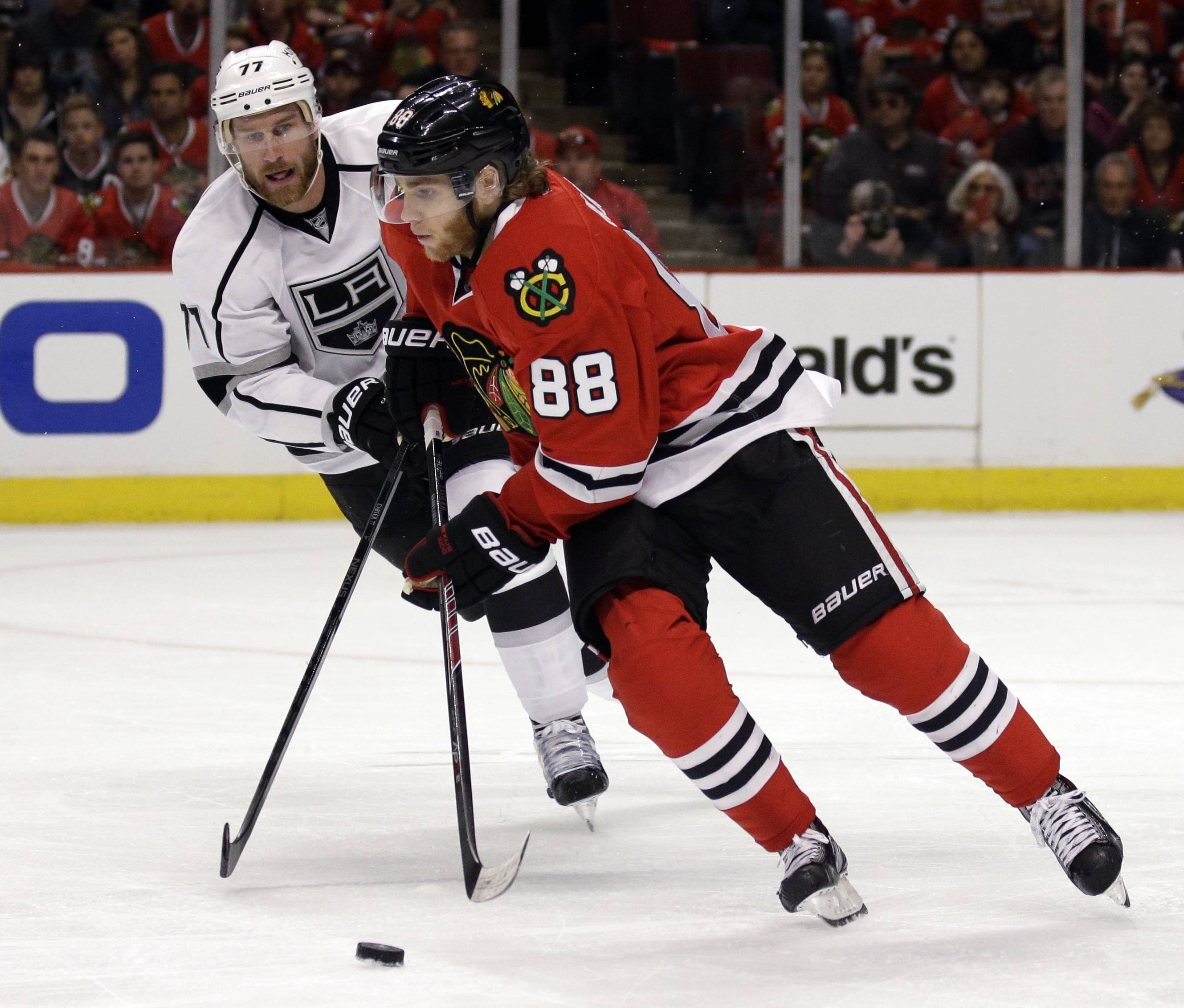 Chicago Blackhawks' Patrick Kane (88), right, controls the puck against Los Angeles Kings' Jeff Carter (77) during the first period in Game 1 of the Western Conference finals in the NHL hockey Stanley Cup playoffs in Chicago on Sunday, May 18, 2014.