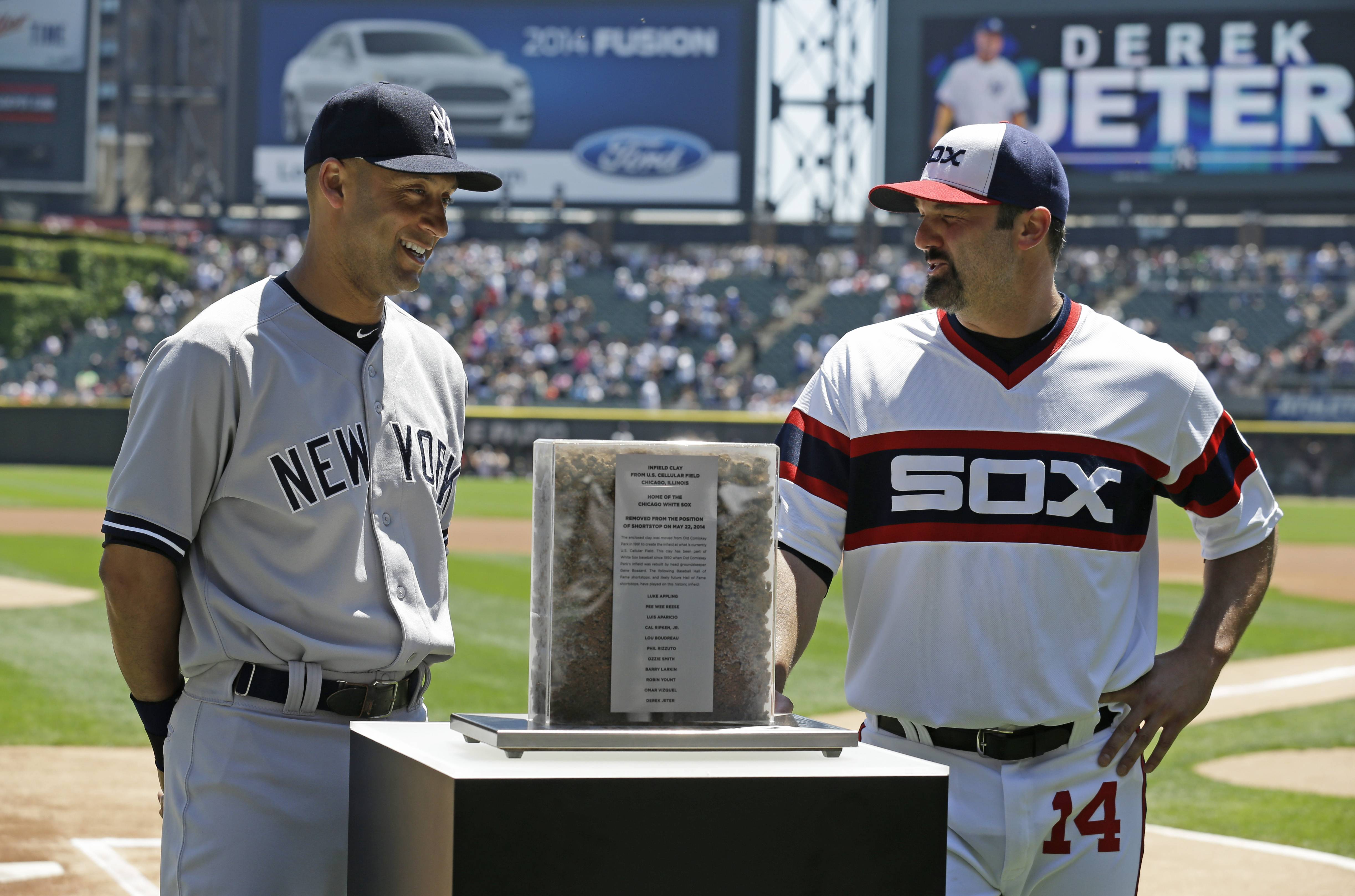 New York Yankees shortstop Derek Jeter, right, is presented with gifts from White Sox designated hitter Paul Konerko before a baseball game in Chicago on Sunday, May 25, 2014.
