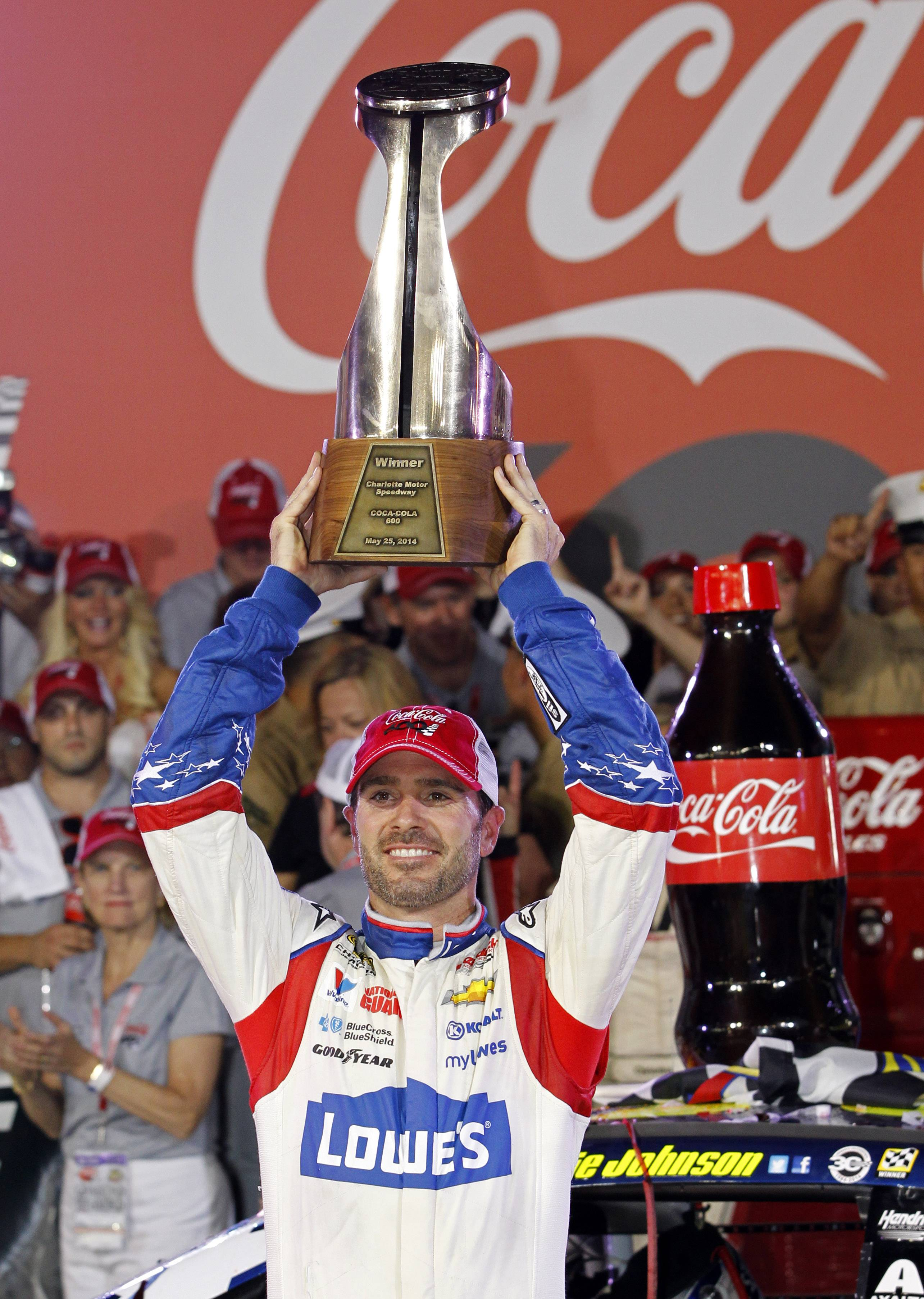 Driver Jimmie Johnson raises the trophy in Victory Lane after winning the NASCAR Sprint Cup series Coca-Cola 600 auto race at Charlotte Motor Speedway in Concord, N.C., Sunday, May 25, 2014.