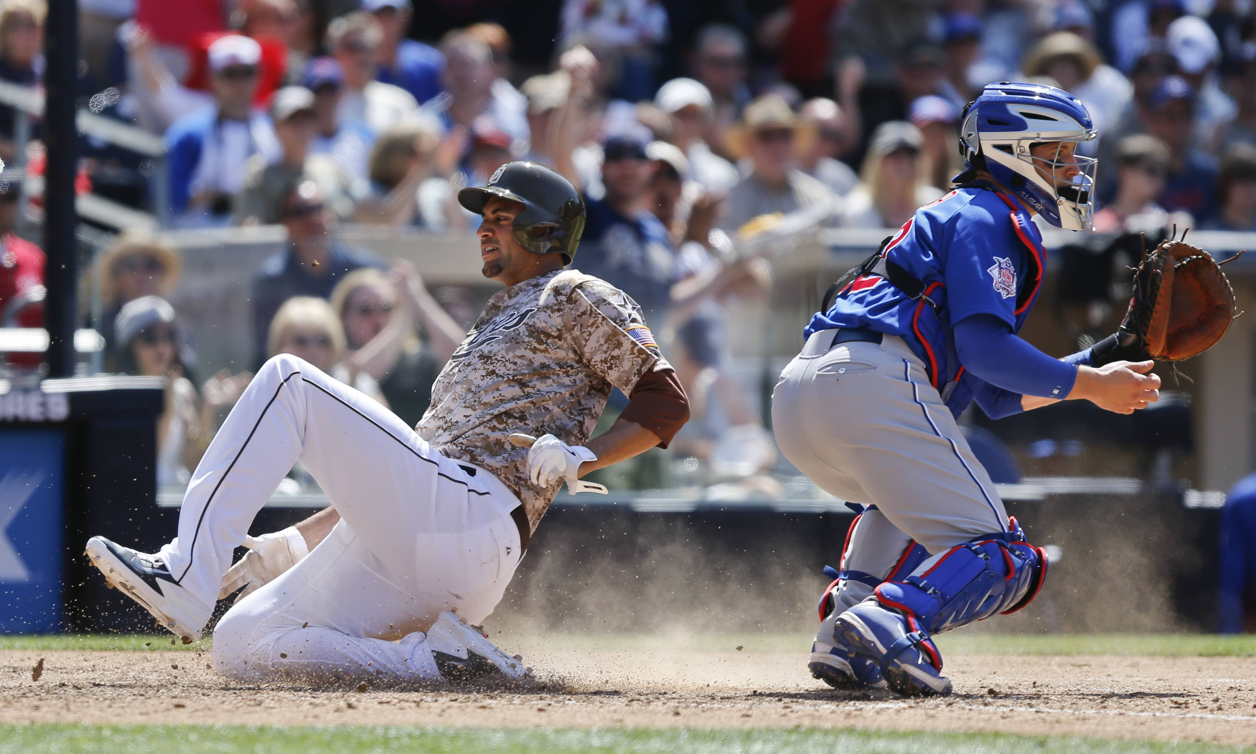 San Diego Padres pinch runner Tyson Ross sides past Chicago Cubs catcher John Baker, right, while scoring against the Chicago Cubs during the sixth inning of a baseball game, Sunday, May 25, 2014, in San Diego.