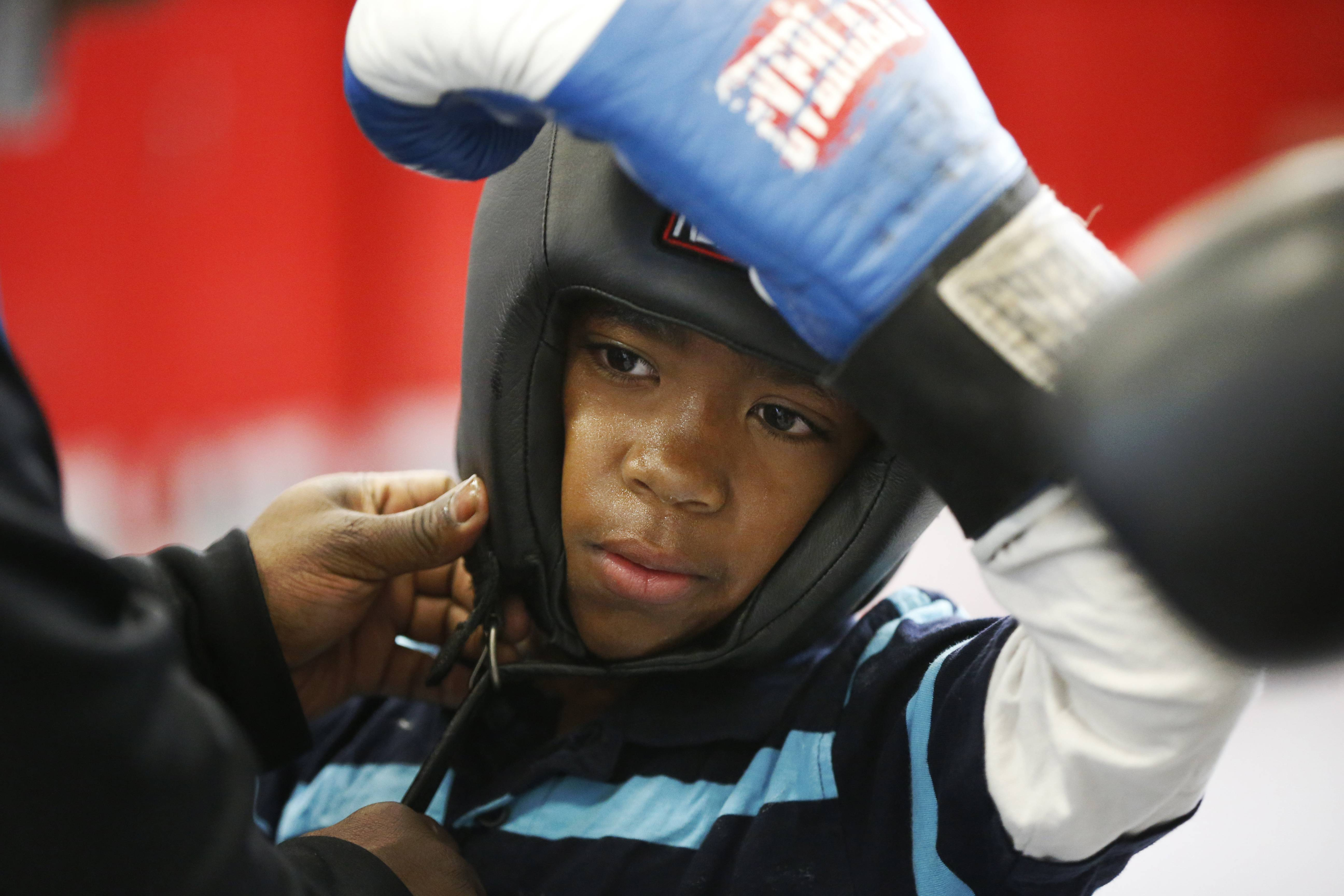 Rahgaleak Bartee, 12, helped with protective gear before boxing in the gym of the DC Promise Neighborhood Initiative (DCPNI) after-school center in the Kenilworth-Parkside neighborhood of Washington.