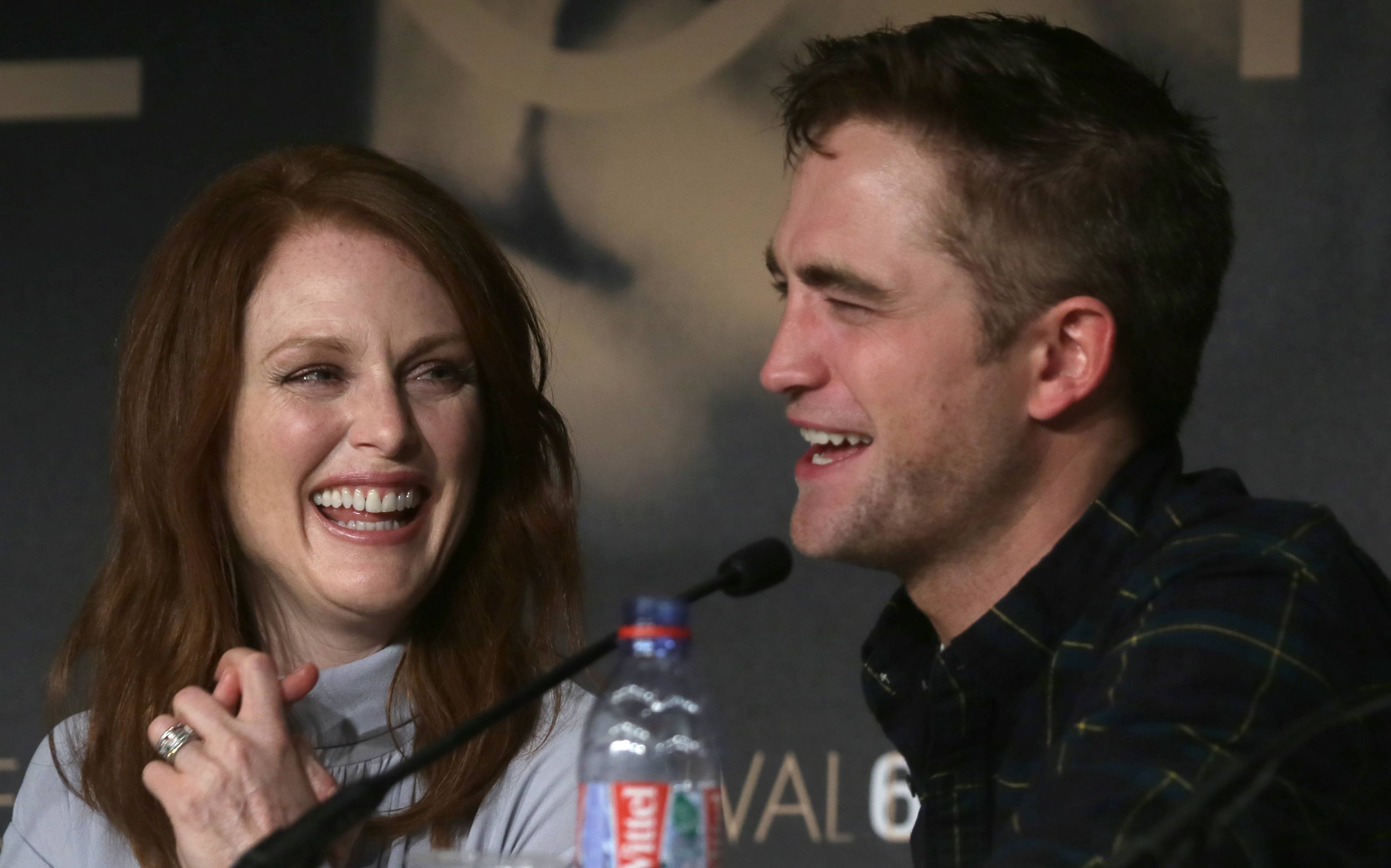 "Actress Julianne Moore, left, and actor Rob Pattinson laugh during a May 19 press conference for ""Maps to the Stars"" at the 67th annual Cannes Film Festival in southern France."