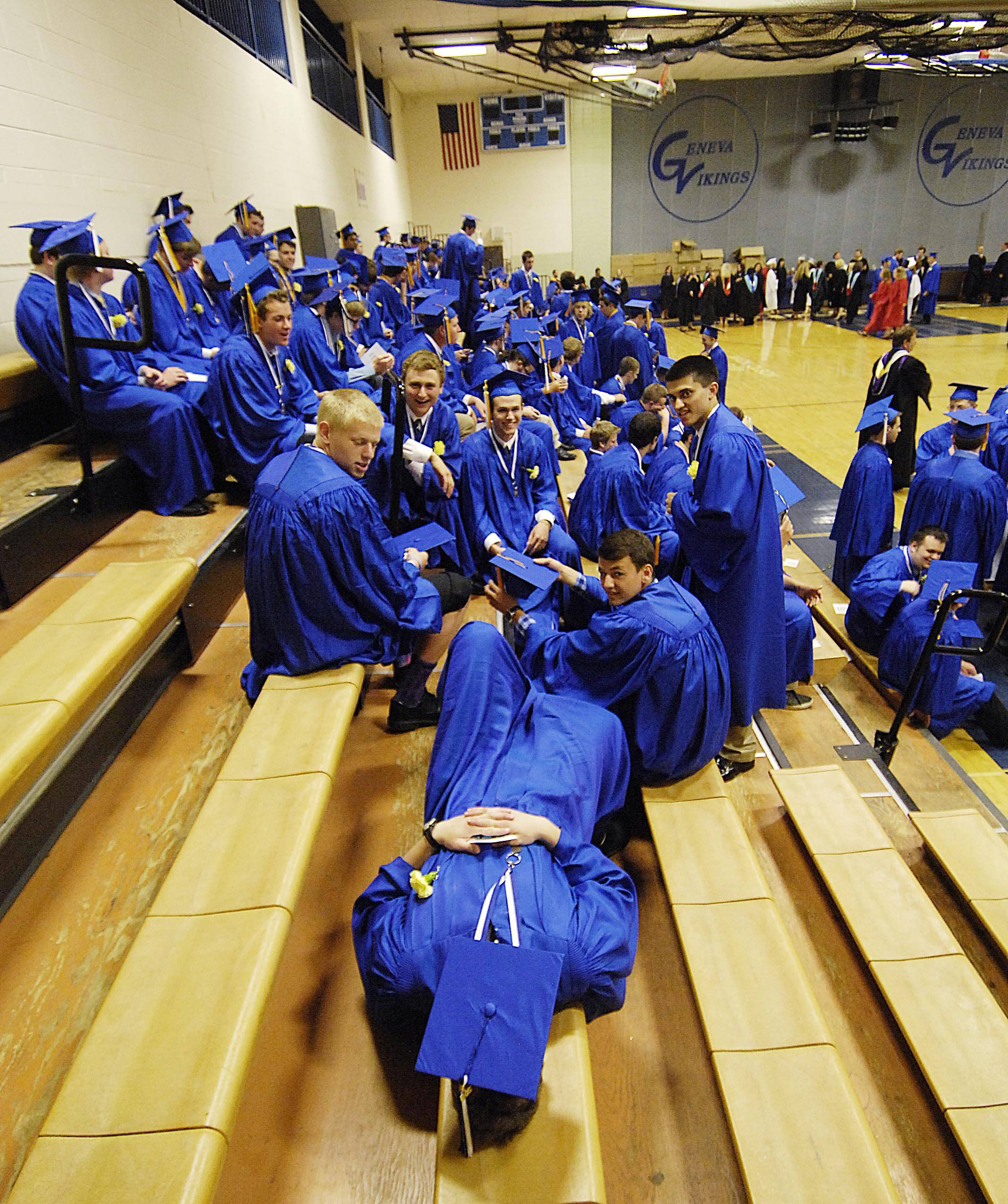 Graduate Ethan Garrity lays back with his mortarboard covering his eyes as he waits with classmates before the Geneva High School 2014 commencement exercises Sunday.