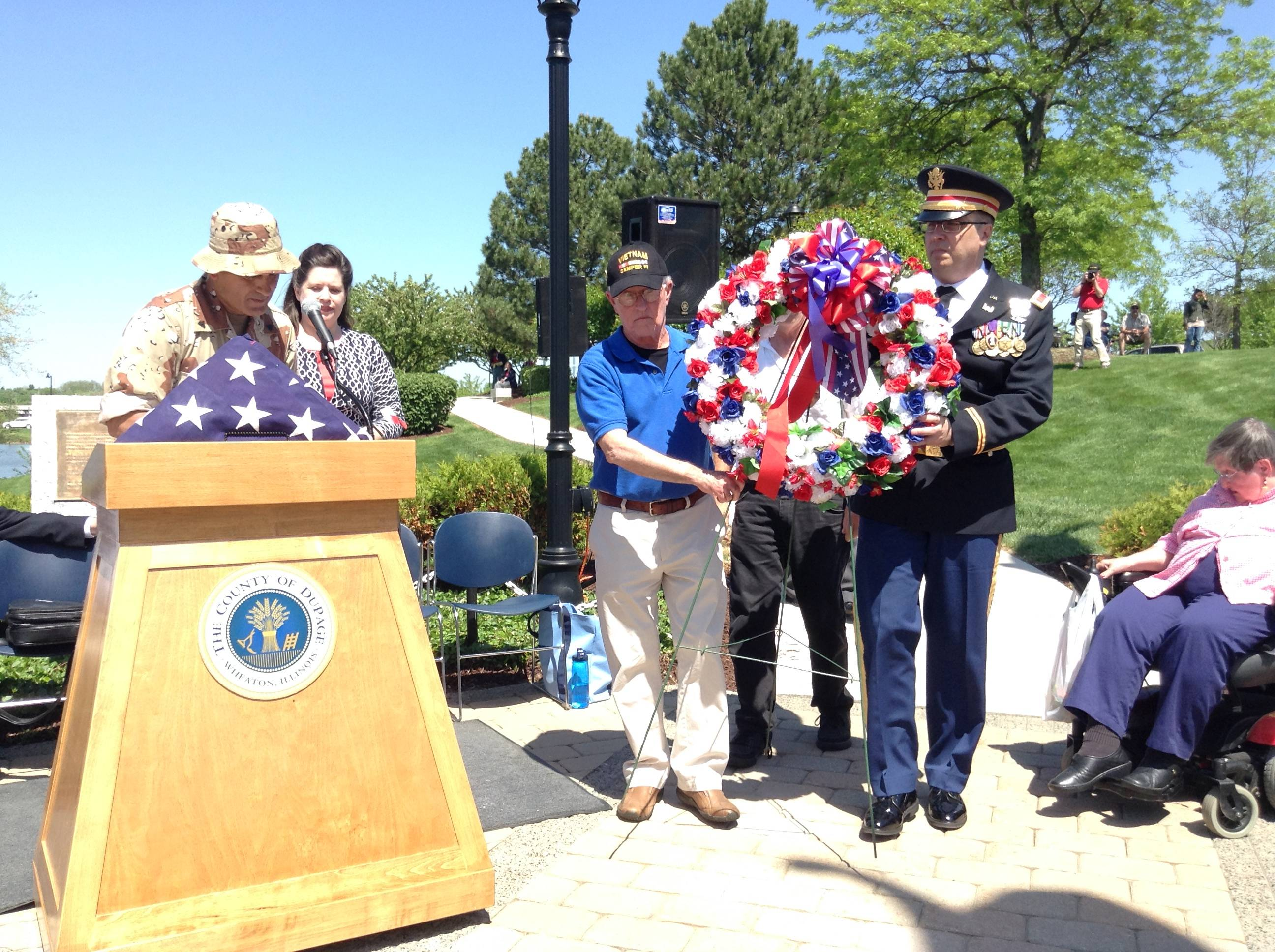 Capt. Ken Jacobs of Wheaton and Bob Adams of Winfield present a memorial wreath at the Memorial Day service Sunday at the DuPage County Veterans' Memorial in Wheaton.