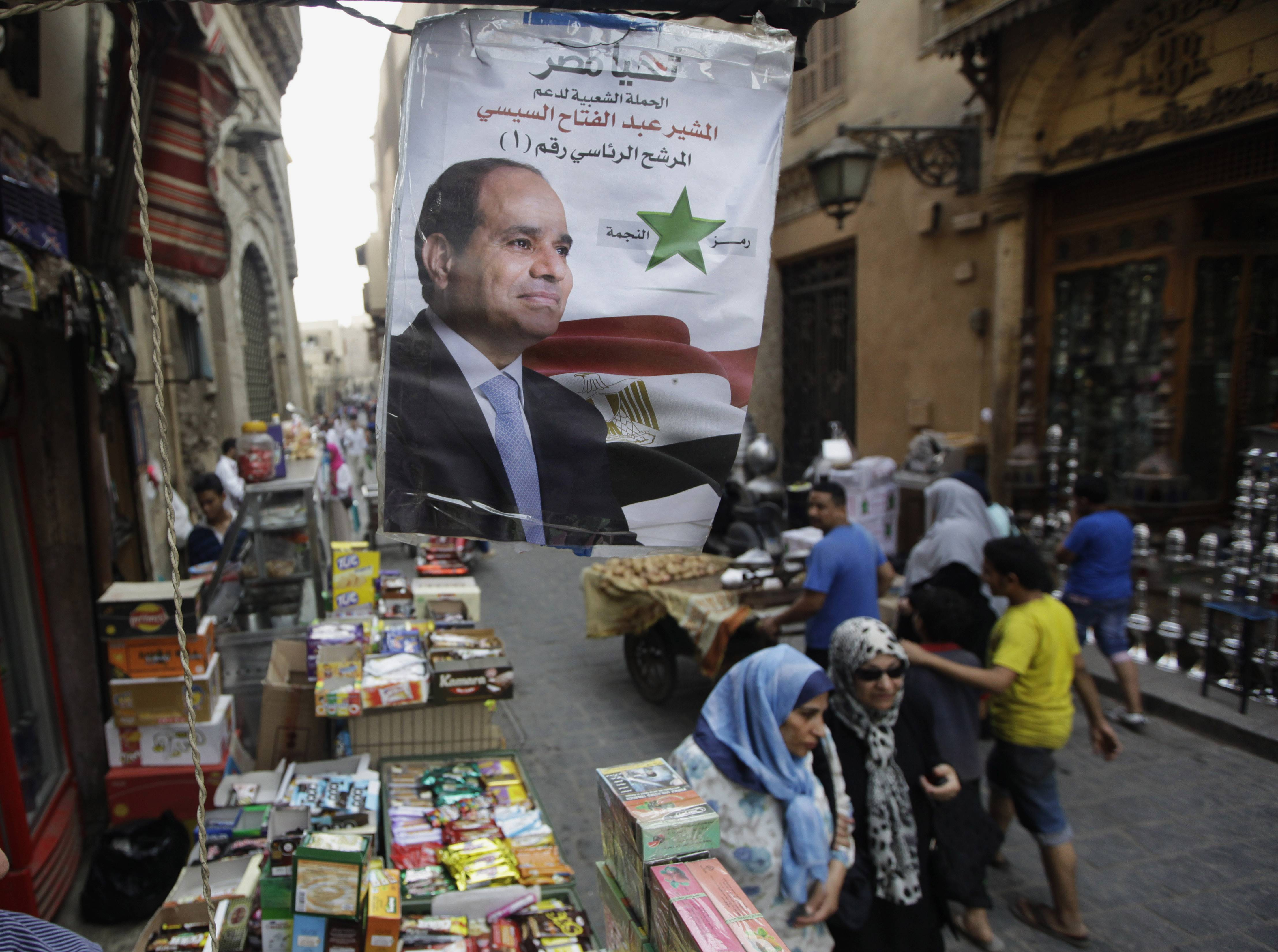 Egyptian shoppers walk under a poster supporting presidential candidate Abdel-Fattah el-Sissi, the country's former military chief, in Cairo, Egypt, Saturday. Considered all but certain to win is el-Sissi, the man who removed the former president, Mohammed Morsi.