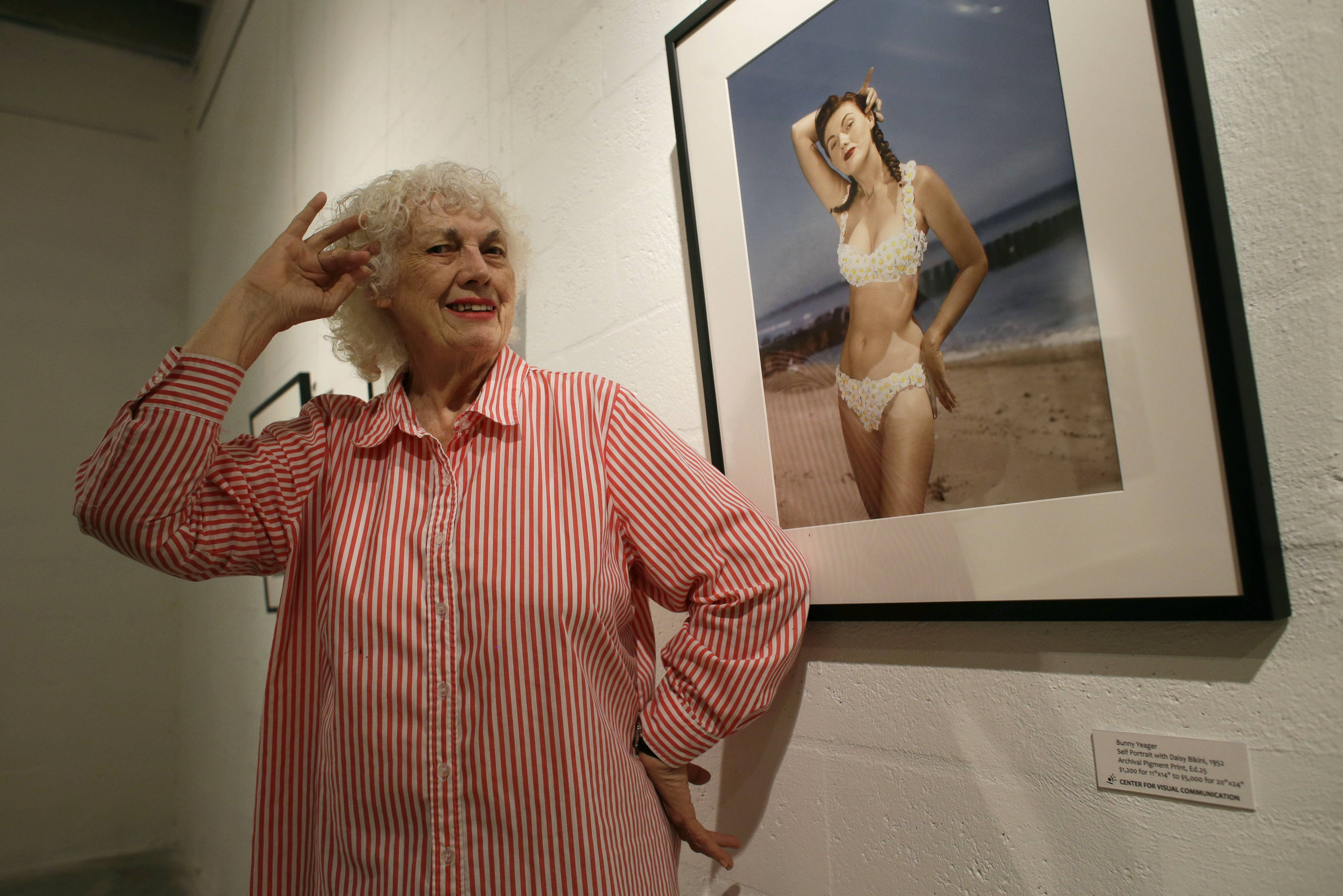 In this April 23, 2013 file photo, photographer Bunny Yeager poses next to a self-portrait photograph taken in 1952 at the Bunny Yeager Studio in Miami. Yeager, a model turned photographer who was most famous for photographing Bettie Page in the 1950s, died Saturday at a Delray Beach hospice. She was 85 years old.
