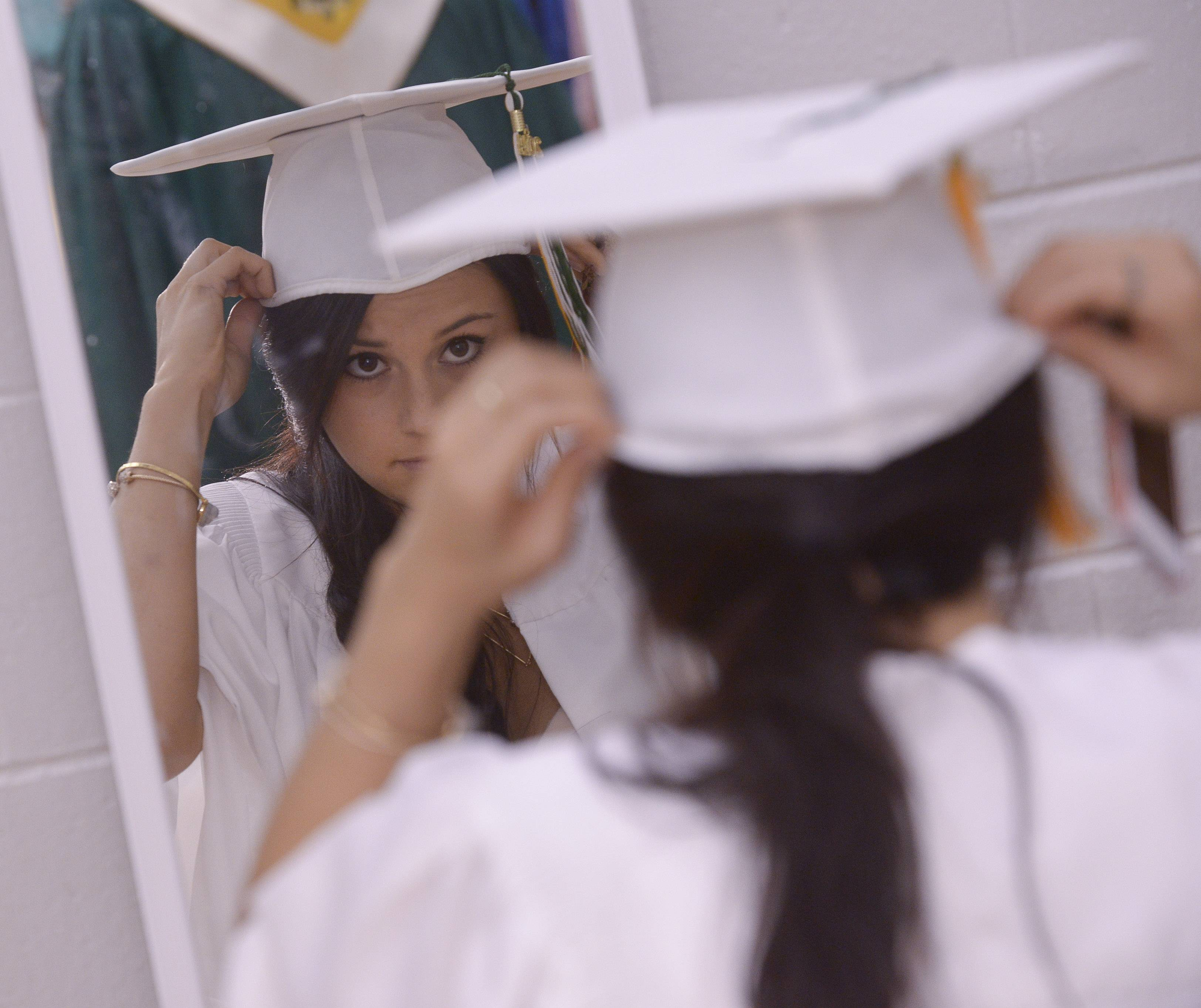 Lea Lokshin checks her cap in a mirror before the start of the Waubonsie Valley High School graduation on Sunday, May 25 at NIU in DeKalb.