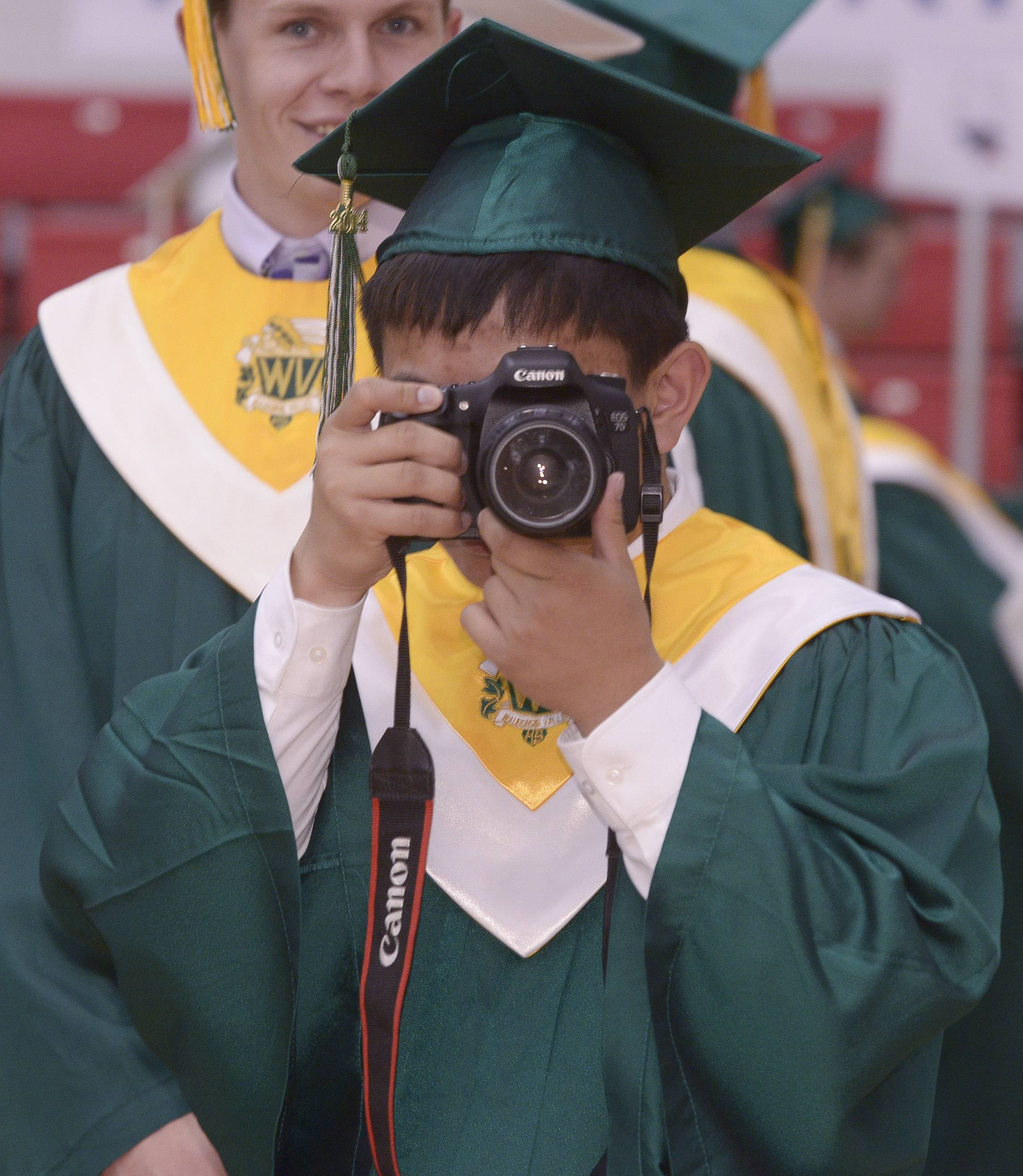 Unlike most of his classmates who use smartphones, Nathan Wang uses a real camera to capture images of his friends and classmates, before the start of the Waubonsie Valley High School graduation on Sunday, May 25 at NIU in DeKalb.