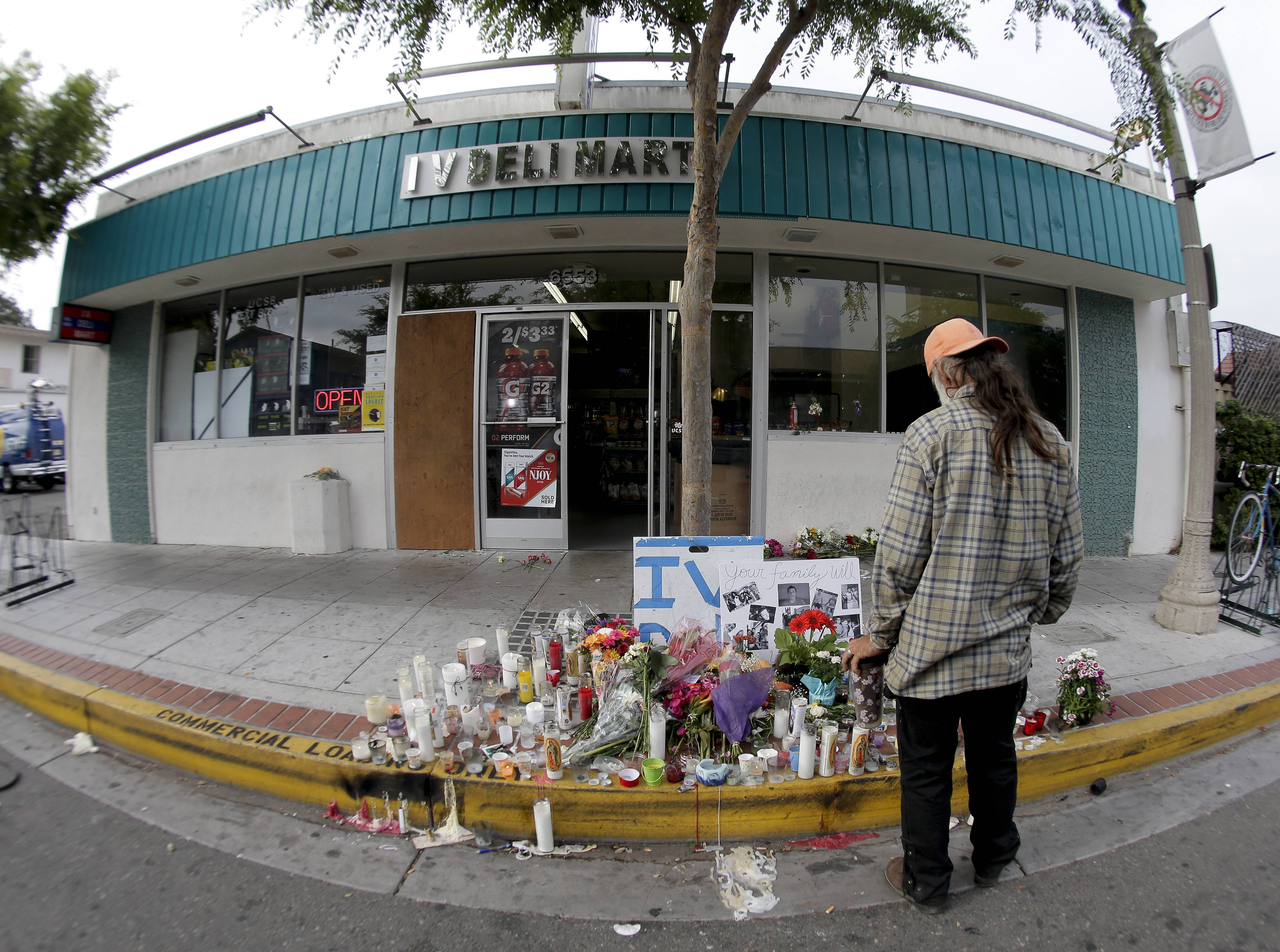 A passer-by pays his respects at a makeshift memorial in front of the IV Deli Mart, Sunday, the scene of a drive-by shooting Friday in the Isla Vista area near Goleta, Calif.