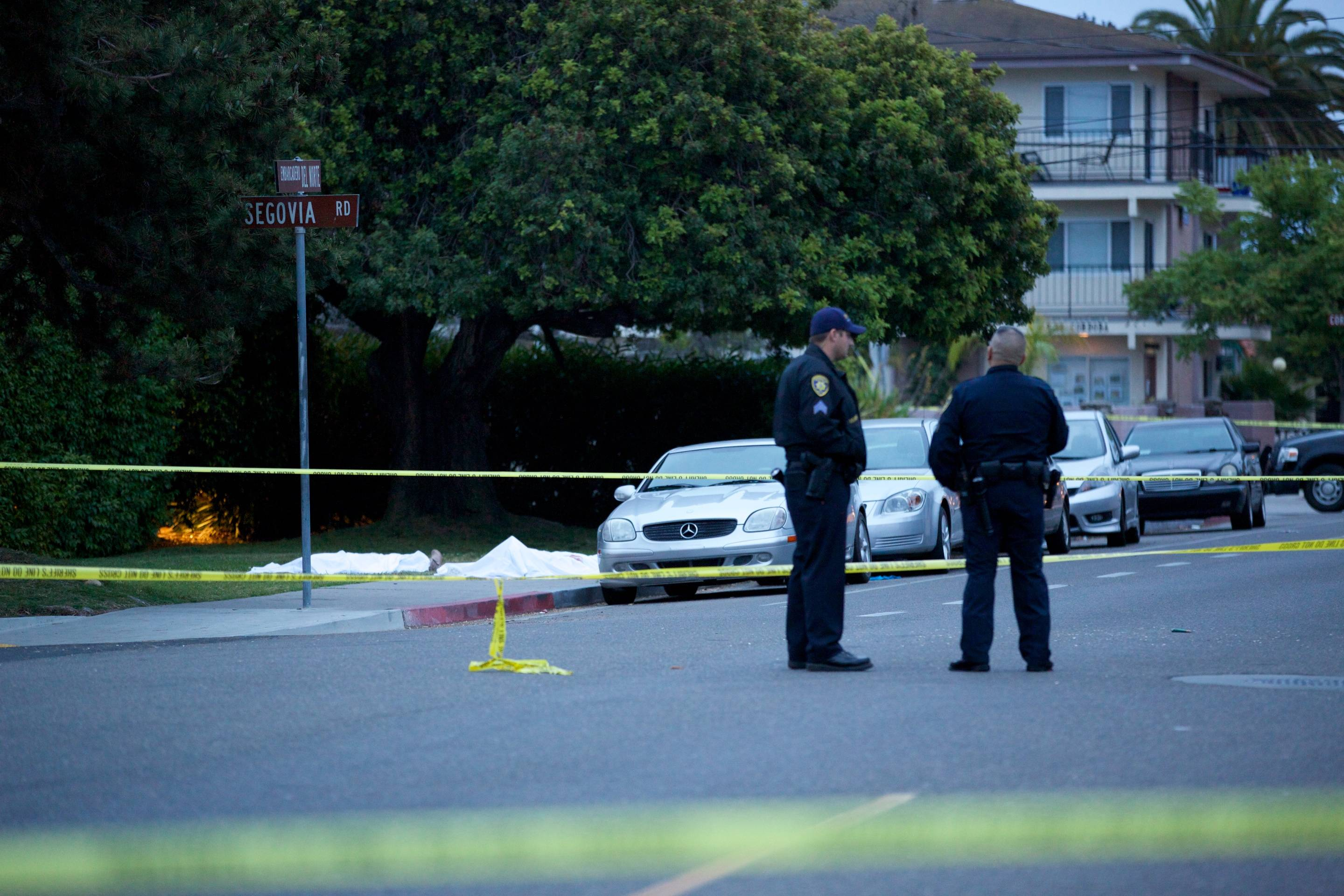 Police wait at the scene after a drive-by shooting left seven people dead, including the attacker, and others wounded on Friday, May 23, 2014, in Isla Vista, Calif. Alan Shifman an attorney for Hollywood director Peter Rodger, who was an assistant director on The Hunger Games, said the family believes Rodger's son, Elliot Rodger, is responsible for the shooting rampage near the Santa Barbara, California, university campus. Authorities have not confirmed the identity of the shooter.