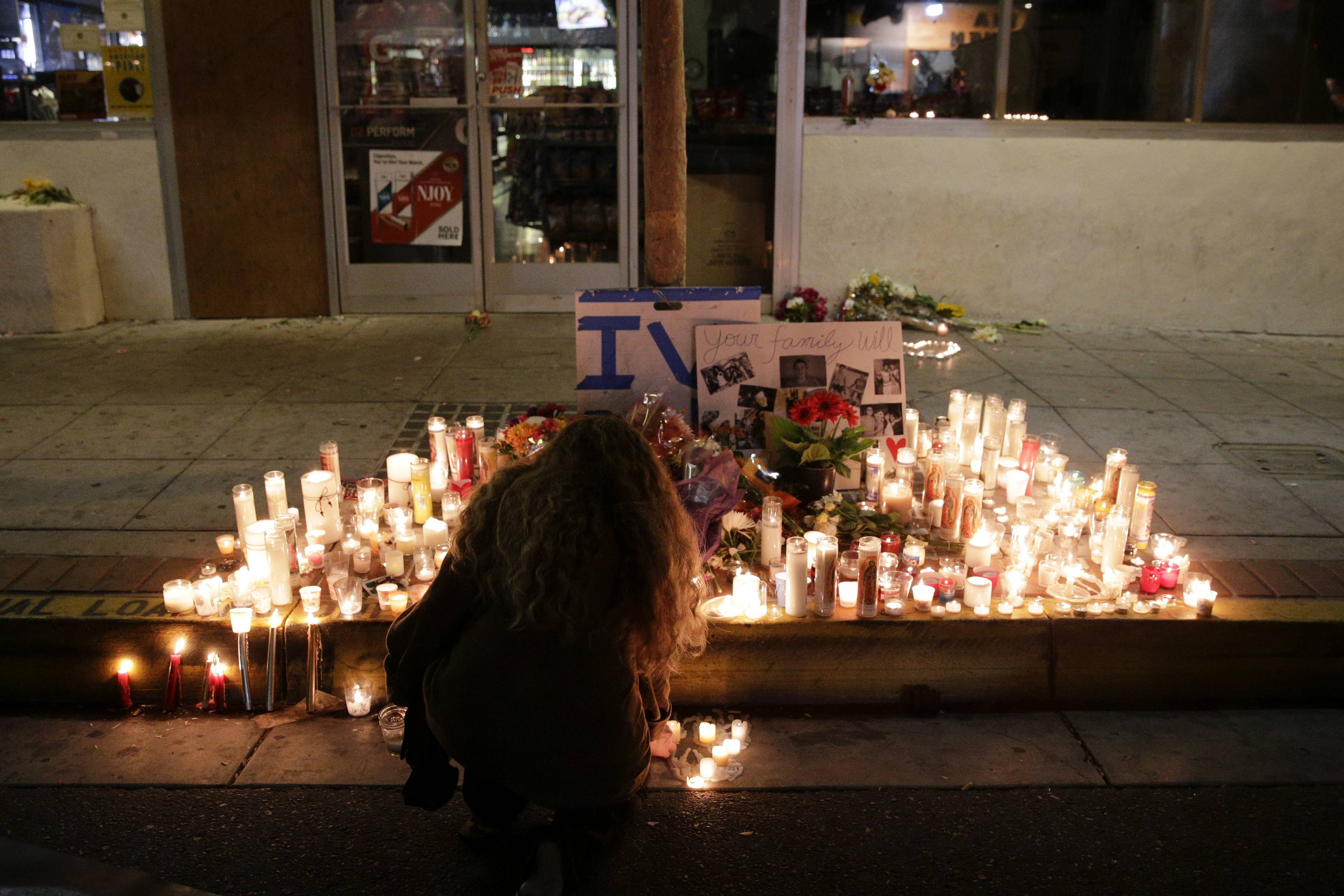A woman places a candle in front of IV Deli Mart, where par of Friday night's mass shooting took place by a drive-by shooter, on Saturday, May 24, 2014, in the beach community of Isla Vista, Calif. Sheriff's officials say Elliot Rodger, 22, went on a rampage near the University of California, Santa Barbara, stabbing three people to death at his apartment before shooting and killing three more in a crime spree through a nearby neighborhood.