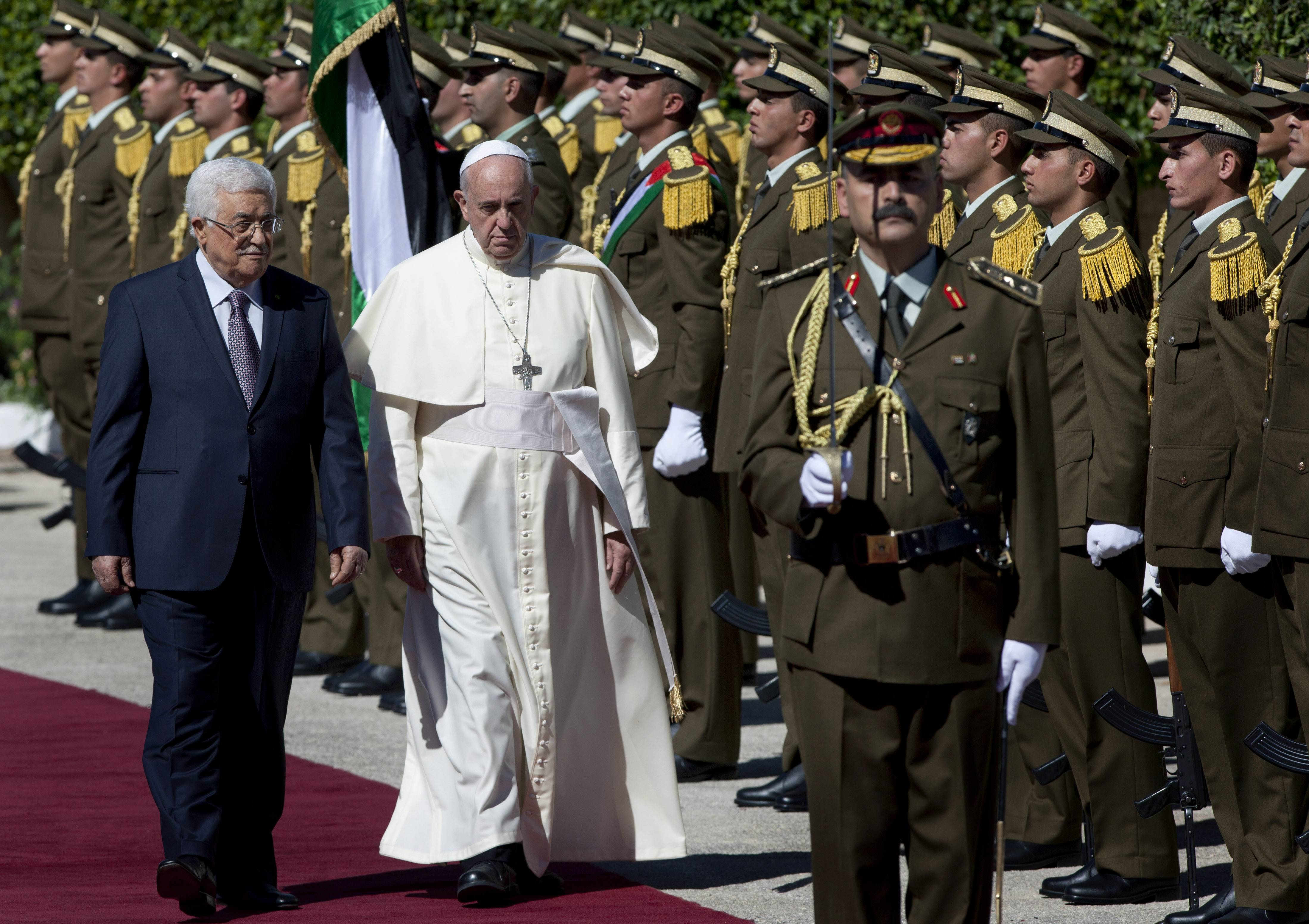 Palestinian President Mahmoud Abbas, left, and Pope Francis inspect an honor guard as Francis arrives at the Palestinian Authority headquarters in the West Bank city of Bethlehem on Sunday.