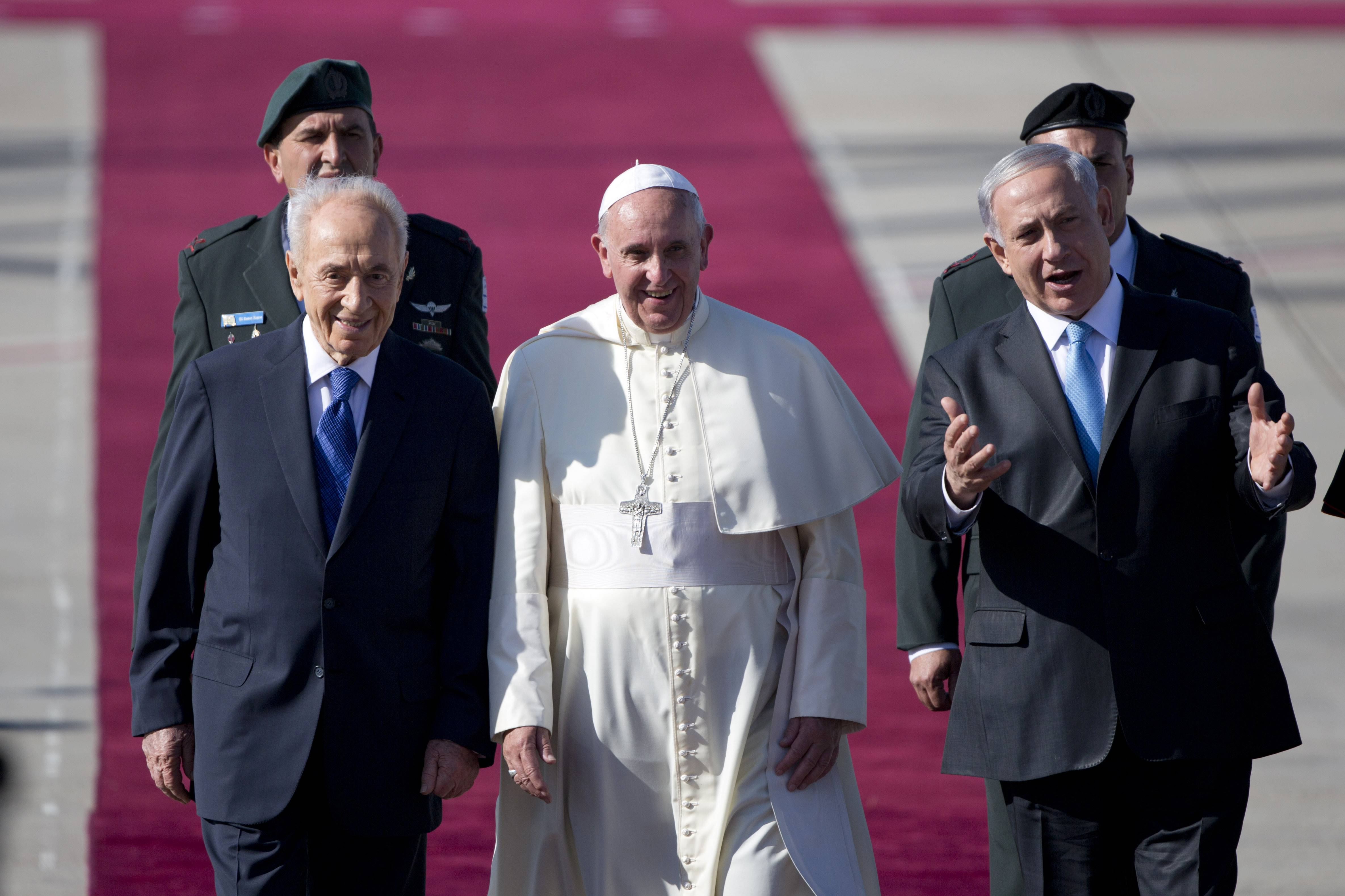 Pope Francis, center, walks with Israeli President Shimon Peres, left, and Prime Minister Benjamin Netanyahu, right, during an  official arrival ceremony at Ben Gurion airport near Tel Aviv, Israel, Sunday.
