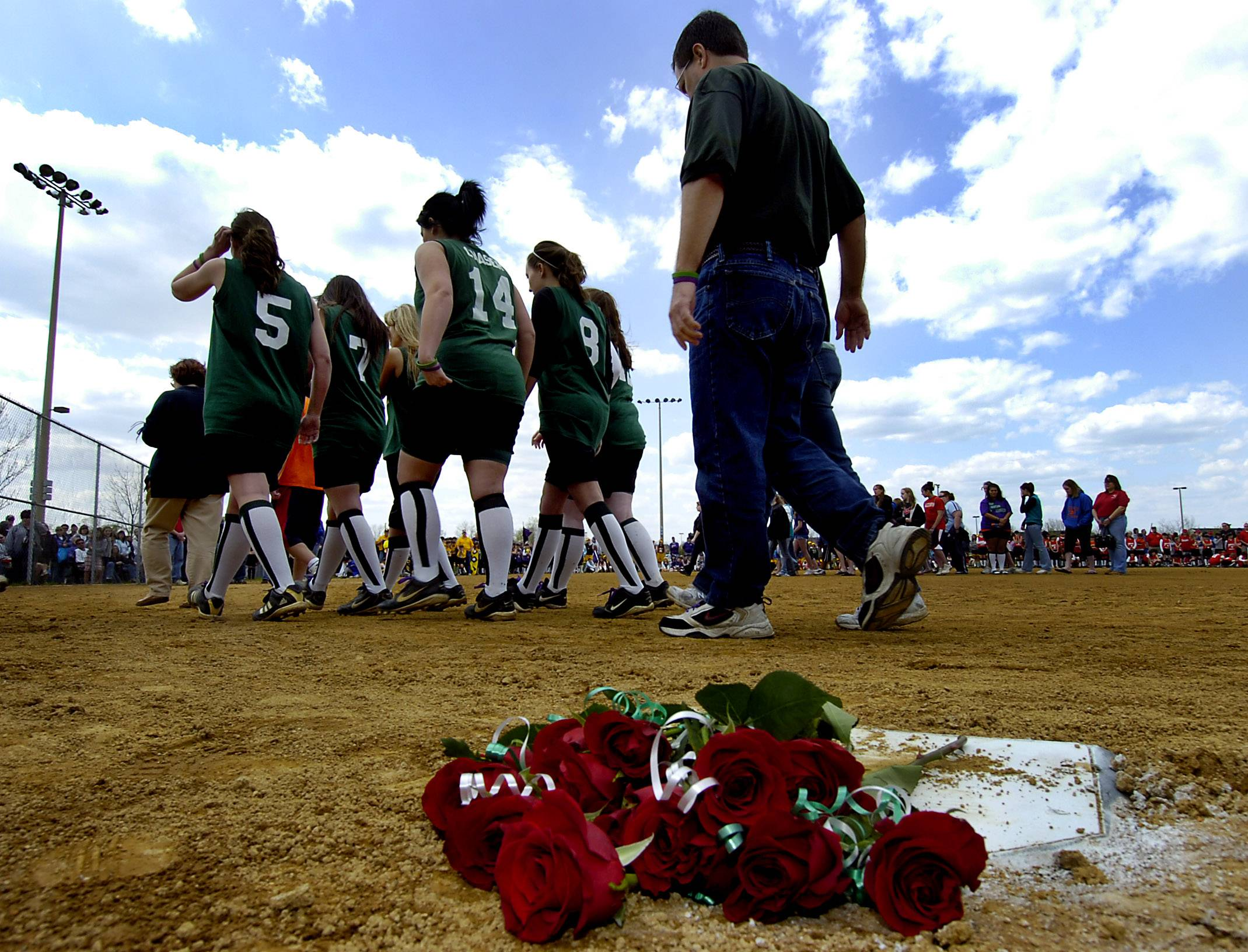 Roses are left at home plate in honor of Laura Engelhardt, star catcher and member of the Blizzard softball team, as her teammates and coach walk away during a tribute held at the 2009 opening ceremony of the league. Laura was killed April 17, 2009.