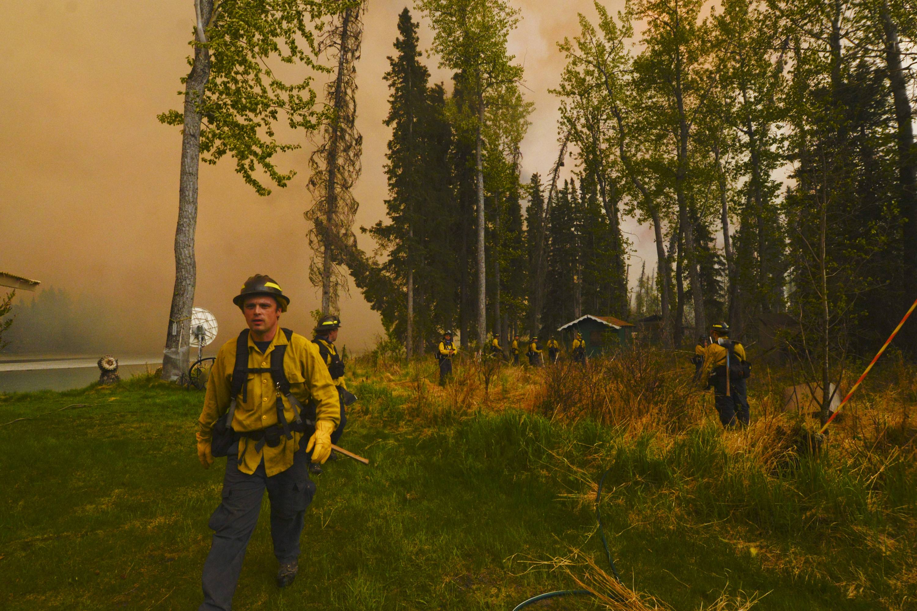 Central Emergency Services firefighters assess whether they can protect a property Sunday, May 25, 2014, in the Funny River community of Soldotna, Alaska. A massive wildfire pushed by wind in Alaska's Kenai Peninsula south of Anchorage continued to explode in size, leading to mandatory evacuations of 1,000 structures, officials said Sunday.