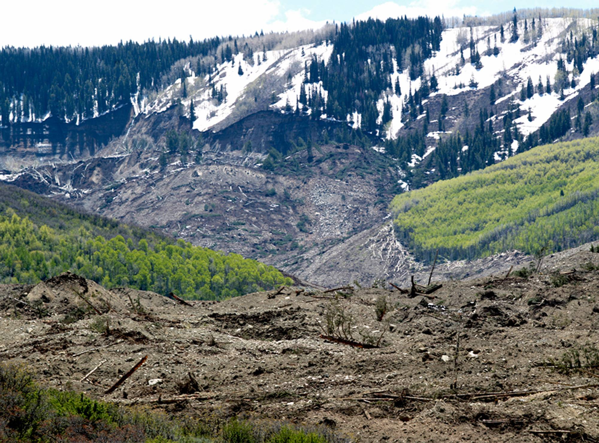 The results of a three-mile long mudslide are piled below Grand Mesa, where the slide started, background, in a remote part of western Colorado on Monday near the small town of Collbran. Rescue teams are searching for three men missing after a half-mile stretch of a ridge saturated with rain collapsed.
