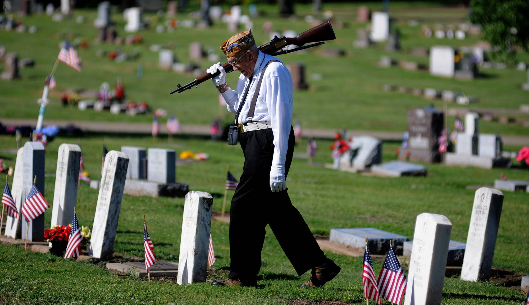 Bill Siebert, of Salina, a member of the VFW Post 1432 Firing Squad, walks through Gypsum Hill Cemetery to join his squad Monday, May 26, 2014, in Salina, Kan. Siebert served during World War II as a soldier in the 80th Infantry Division in France and Germany.