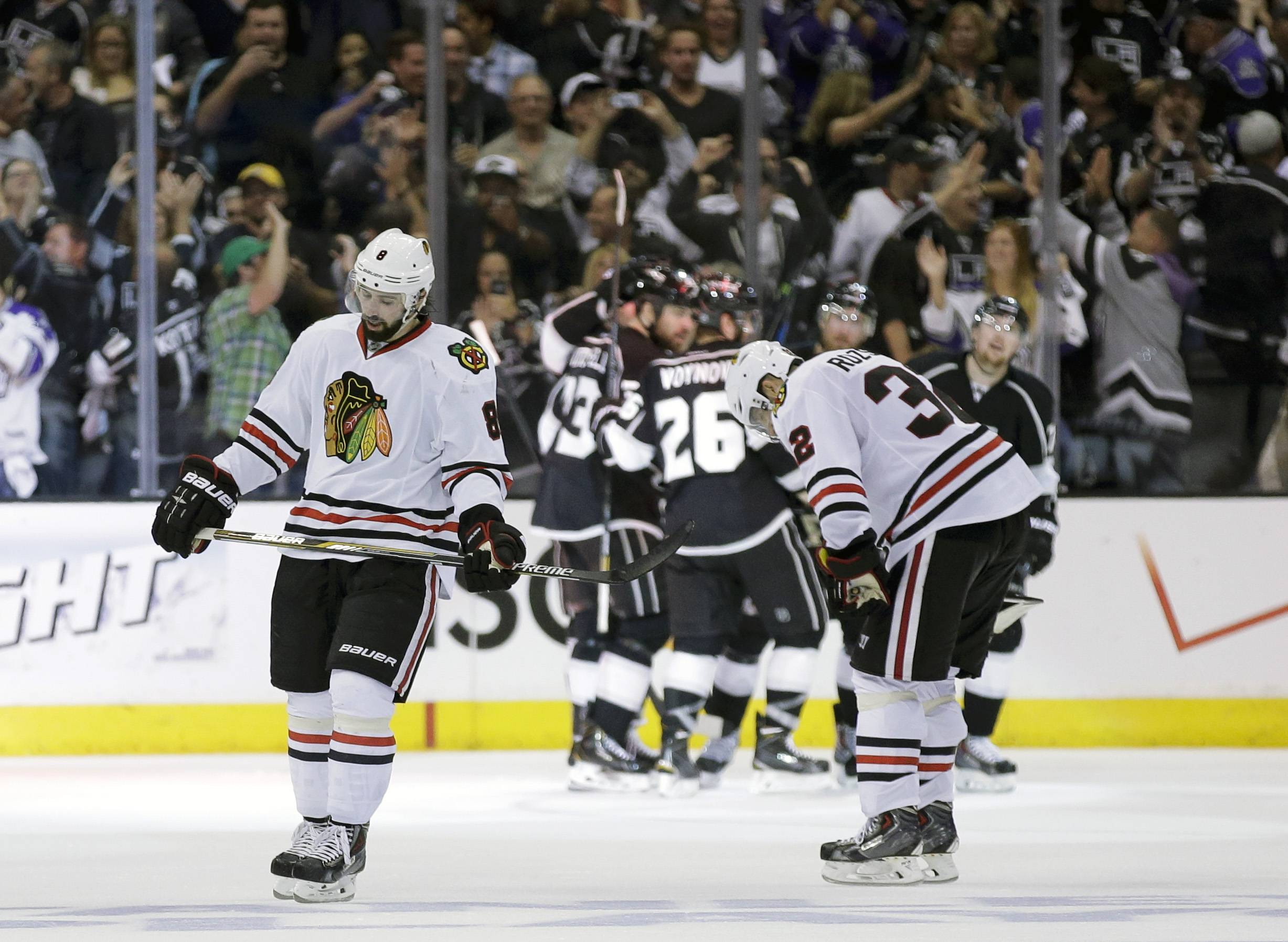Chicago Blackhawks defenseman Nick Leddy, left, and defenseman Michal Rozsival hang theirs heads as members of the Los Angeles Kings celebrate center Jeff Carter's empty net goal during the third period of Game 4 of the Western Conference finals of the NHL hockey Stanley Cup playoffs in Los Angeles, Monday, May 26, 2014. The Kings won 5-2.