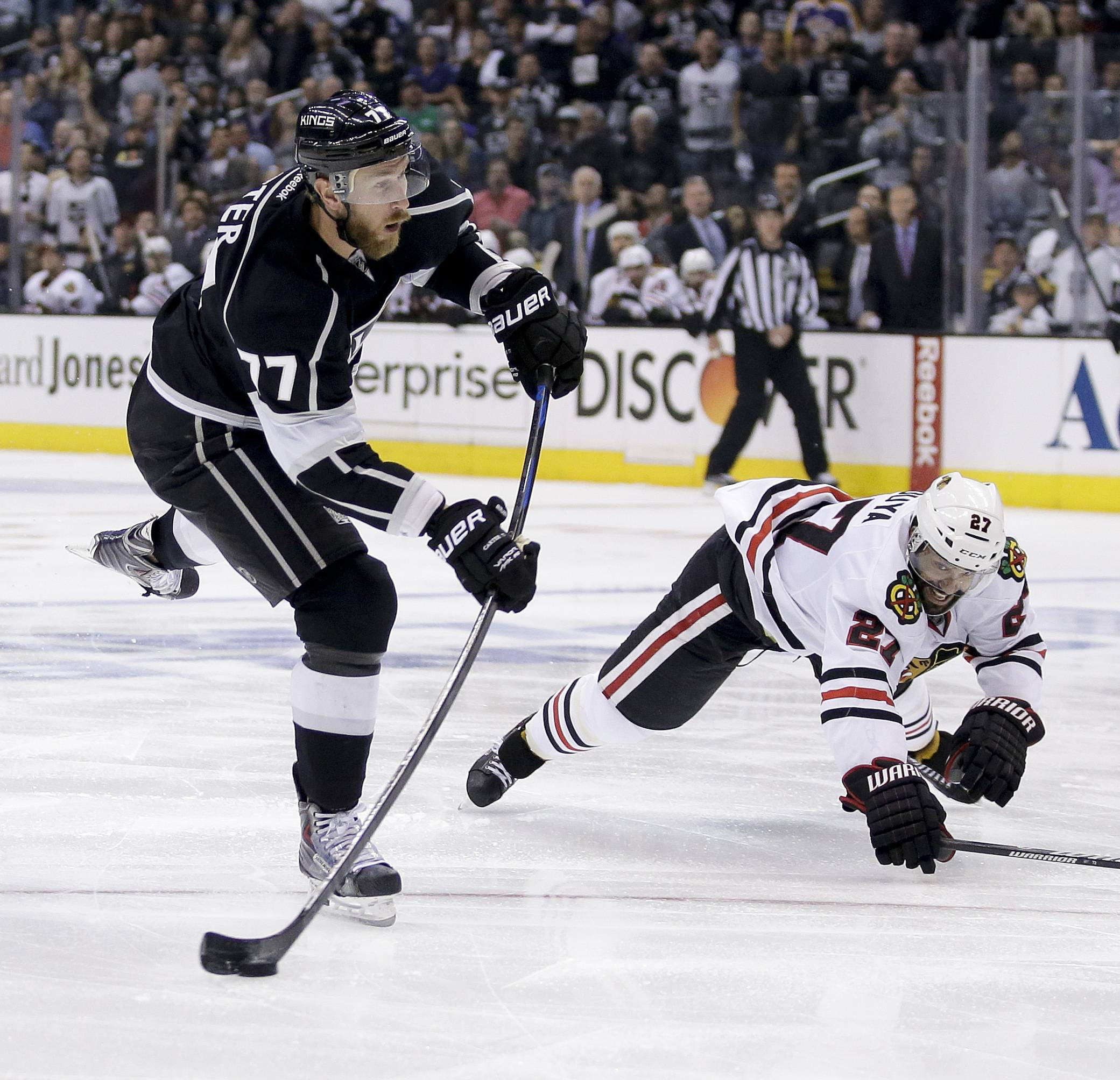 Los Angeles Kings center Jeff Carter, left, shoots past Chicago Blackhawks defenseman Johnny Oduya during the second period of Game 4 of the Western Conference finals of the NHL hockey Stanley Cup playoffs in Los Angeles, Monday, May 26, 2014.