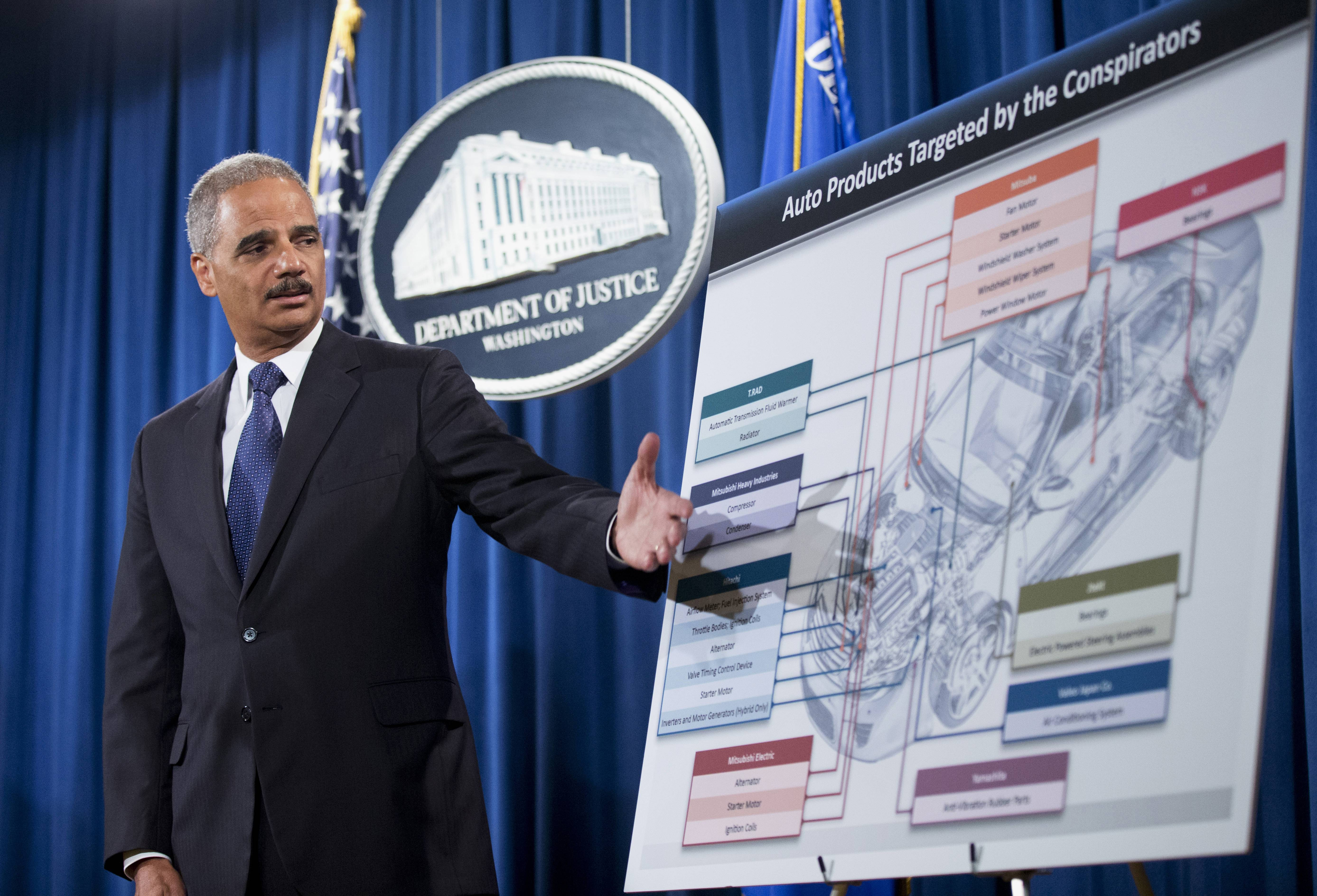 This Sept. 26, 2013, file photo shows Attorney General Eric Holder pointing to an illustration of auto parts during a news conference at the Justice Department in Washington. A federal investigation into price fixing in the auto parts industry, made public four years ago with FBI raids in the Detroit area, has mushroomed into the largest antitrust investigation in Justice Department history -- and authorities say it's not over yet.