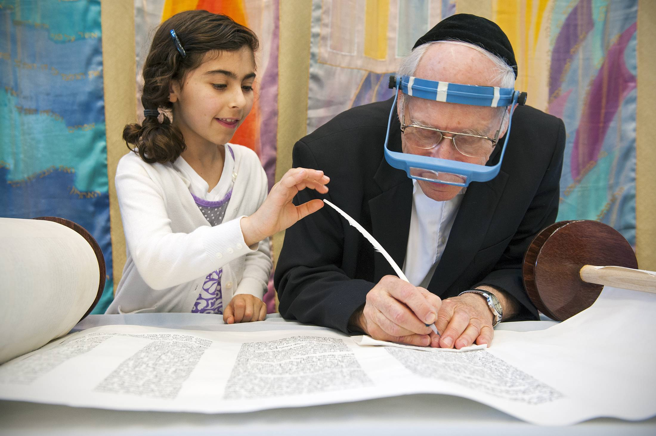 Mira Epstein, 8, left, lightly touches the feathered pen that her grandfather Richard Epstein uses to finish the final details of a Torah at Chabad of Potomac in Potomac, Md.