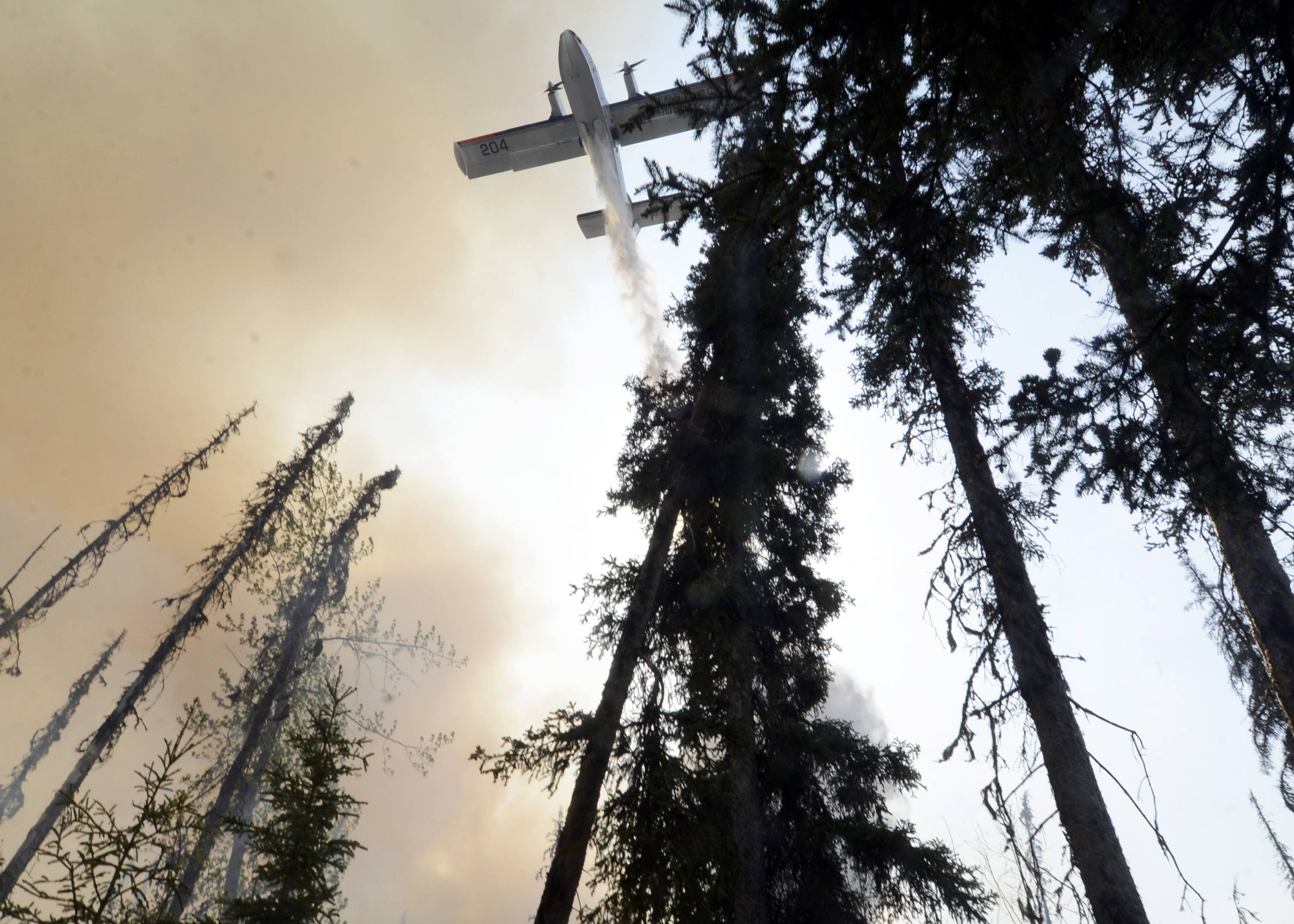 A plane sprays over a portion of a wildfire Sunday, May 25, 2014, in the Funny River community of Soldotna, Alaska. A massive wildfire pushed by wind in Alaska's Kenai Peninsula south of Anchorage continued to explode in size, leading to mandatory evacuations of 1,000 structures, officials said Sunday.