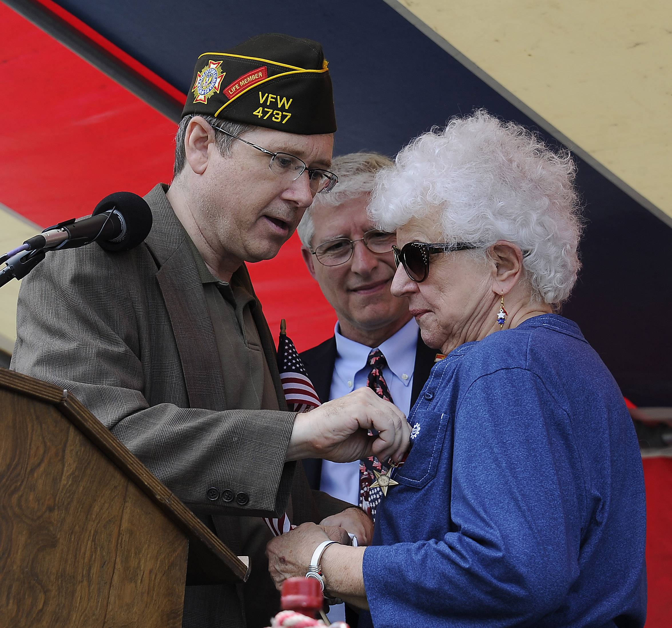 Mark Welsh/mwelsh@dailyherald.comSenator Mark Kirk pins the Bronze Star on Nancy Clauser of Mount Prospect, next-of-kin and first cousin to John Bock, a World War II veteran, during the ceremony at the Arlington Heights Memorial Day event on Monday.
