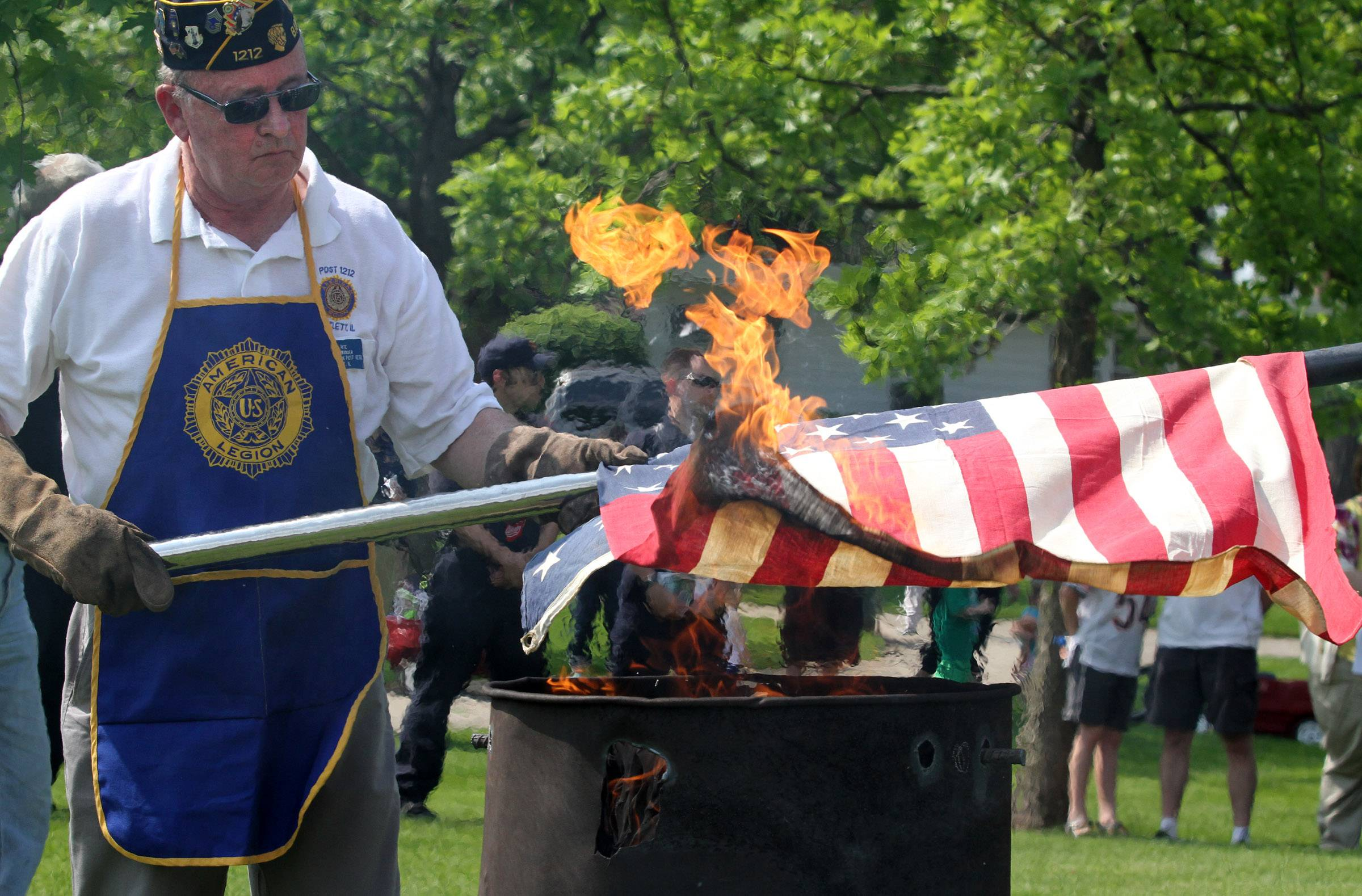 Brian Pate of Bartlett with American Legion Post 1212 lowers an old, worn American flag into a barrel of flames during a flag retirement ceremony held by Bartlett VFW Post 11018 at Bartlett Park on Memorial Day. Thirteen flags were retired in honor of the first 13 colonies.