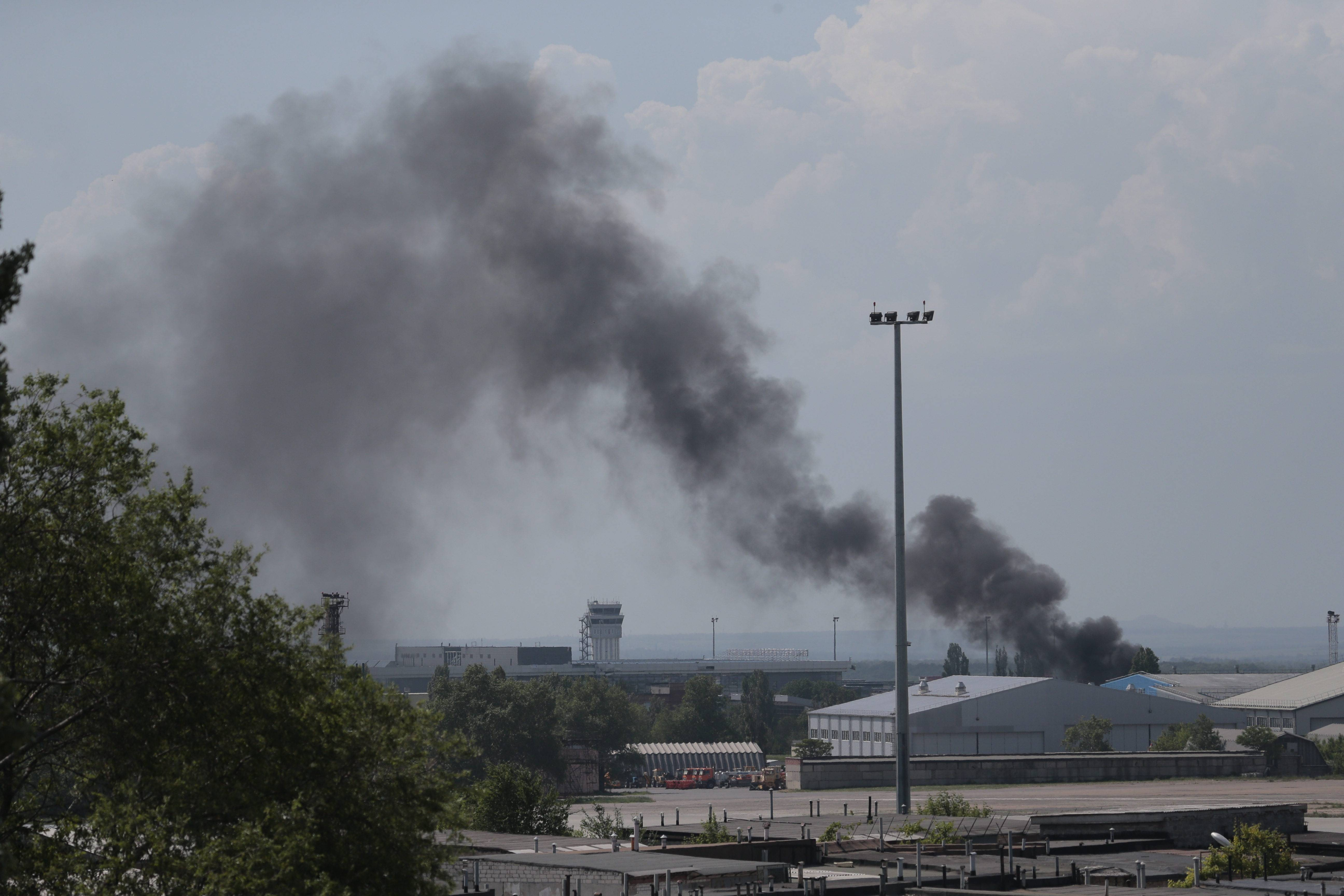 Smoke rises at the airport outside Donetsk, Ukraine, Monday, May 26, 2014. Ukraine's military launched airstrikes Monday against the separatists who had taken over the airport in the eastern city of Donetsk, suggesting that fighting in the east is far from over.
