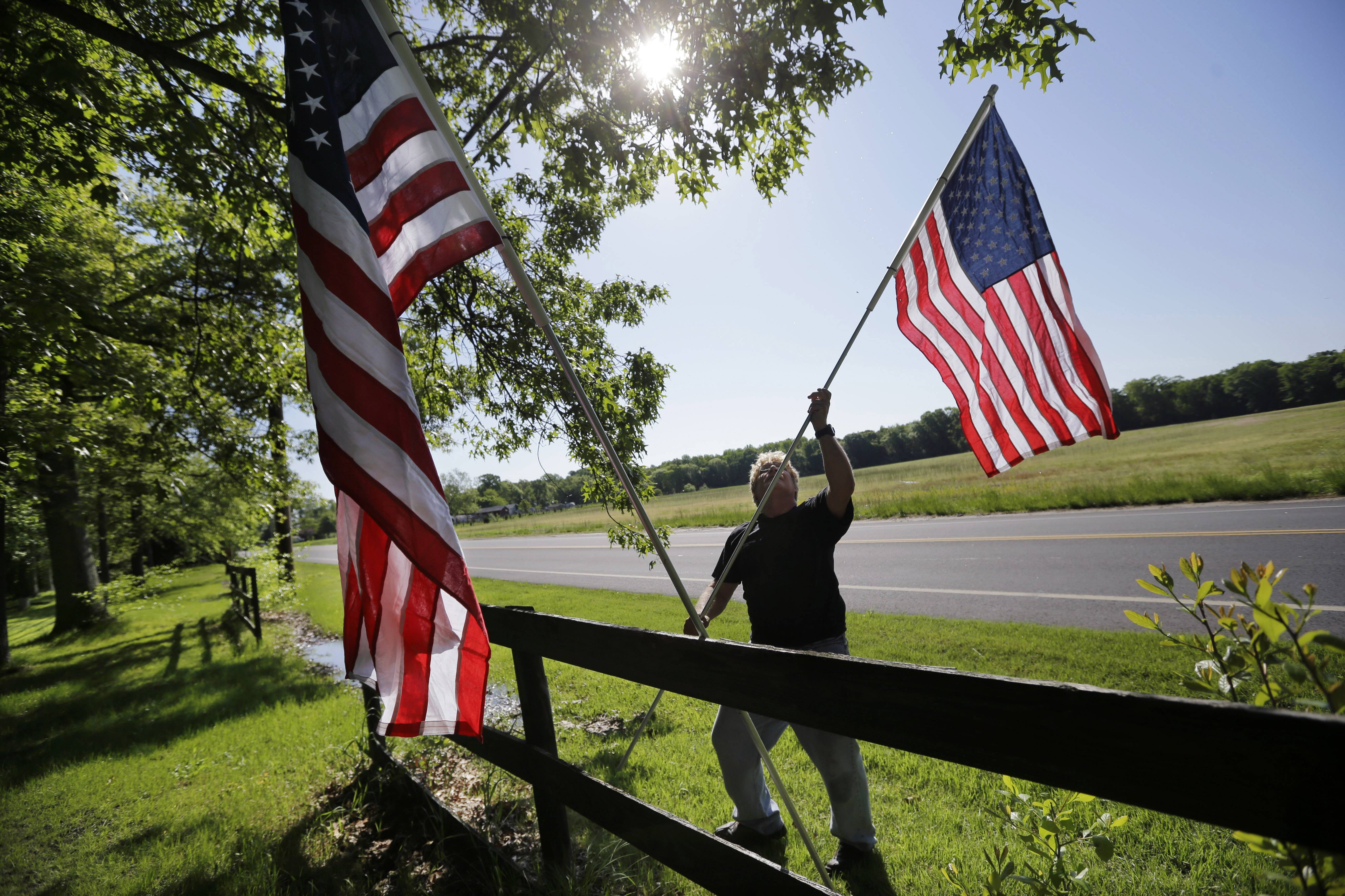 Bob Petersen places flags along a fence for the Memorial Day weekend, at his home in the Cream Ridge section of Upper Freehold, N.J., Sunday, May 25, 2014.