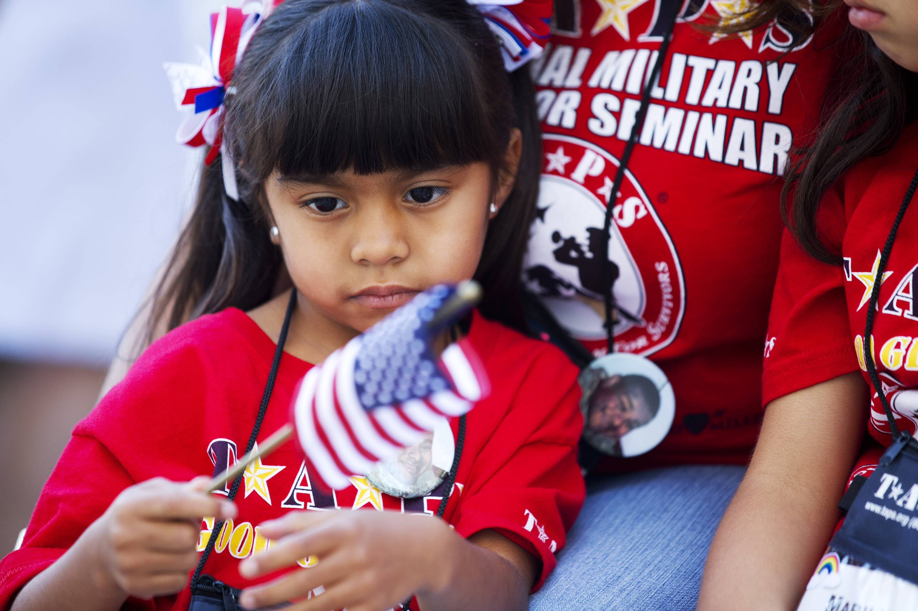 Mariana Cardenaz, 5, of San Diego, Calif., looks at a small U.S. flag while attending a Memorial Day event at Arlington National Cemetery Monday, May 26, 2014. Her father, Army Staff Sgt. Michael Cardenaz was killed serving in Afghanistan in 2010.