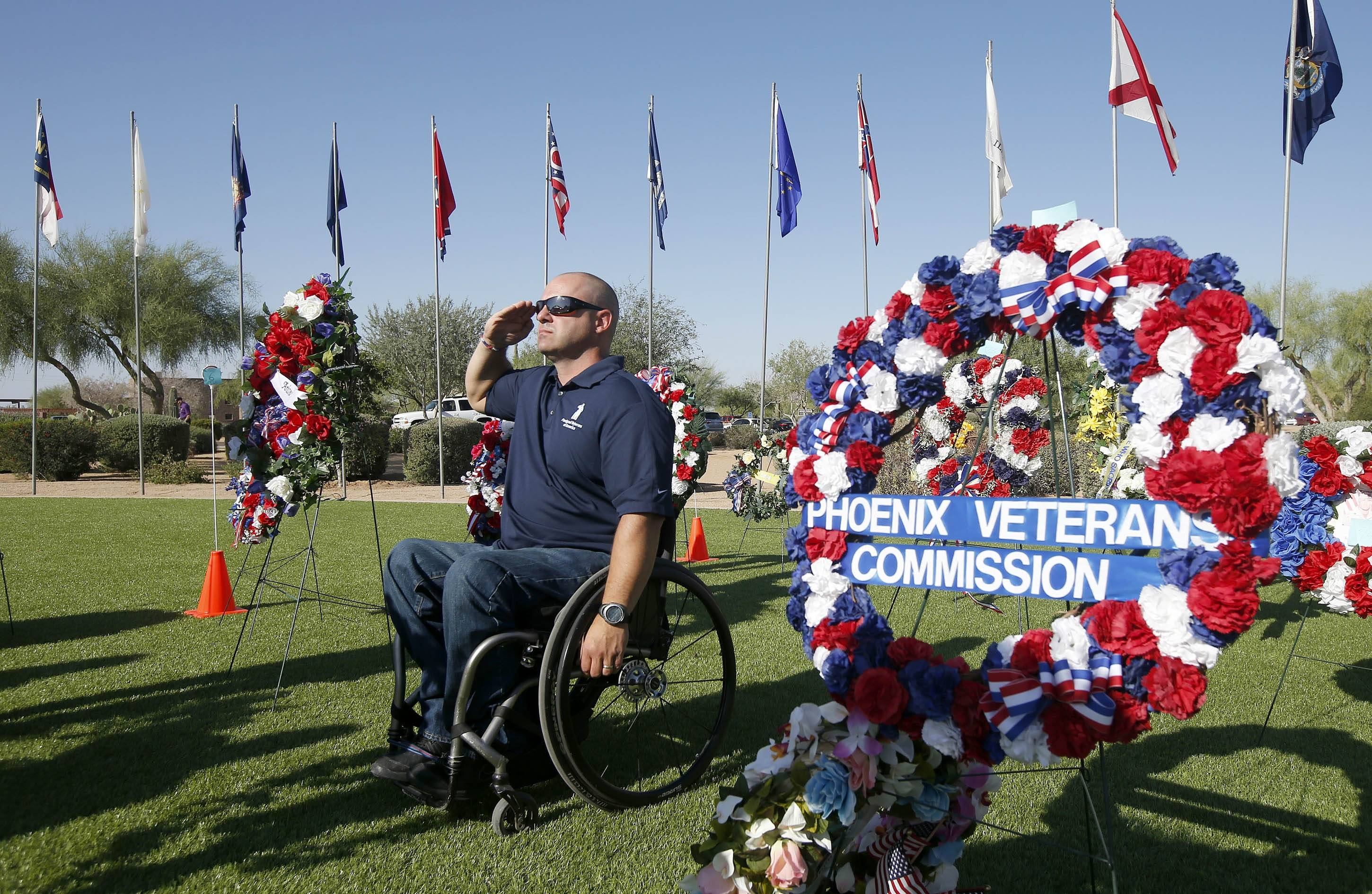 Former Army Ranger veteran John Tuzzolino, president of the Arizona Chapter of Paralyzed Veterans of America, salutes during the national anthem during a Memorial Day ceremony at the National Memorial Cemetery of Arizona on Monday, May 26, 2014, in Phoenix.