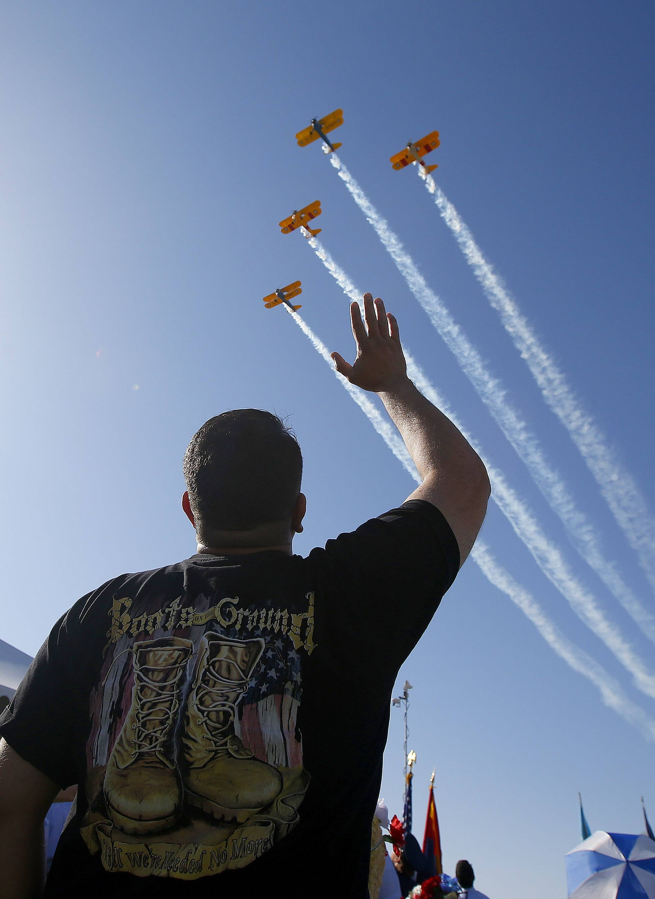 An Iraq War veteran waves as planes fly over during a Memorial Day ceremony at the National Memorial Cemetery of Arizona, Monday, May 26, 2014, in Phoenix.