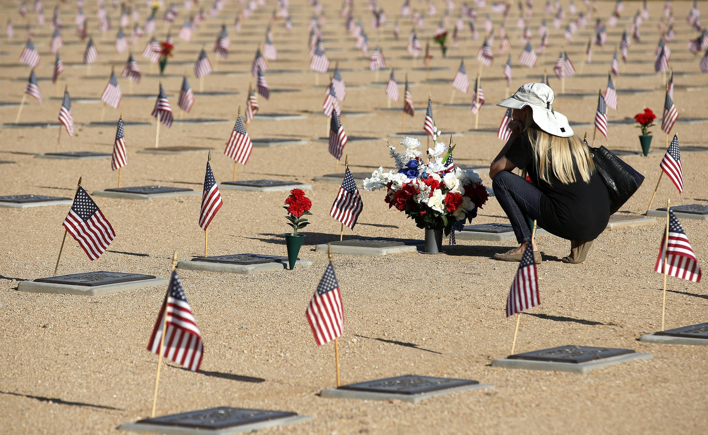 A visitor to the National Memorial Cemetery of Arizona pauses at a grave on Memorial Day, Monday, May 26, 2014, in Phoenix.