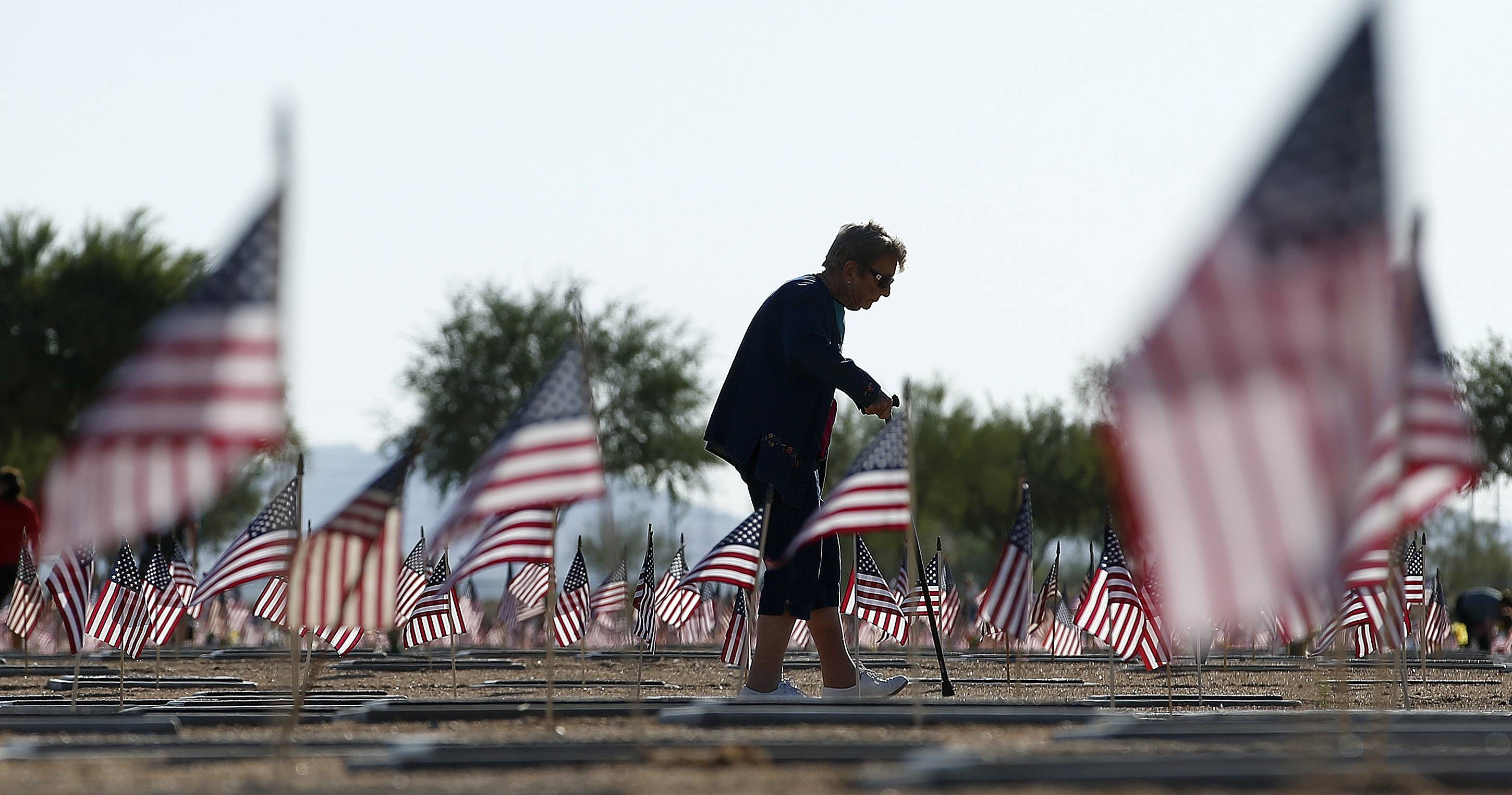 Raymonde Murphy walks past the flag-adorned graves after visiting the grave of her husband, William Murphy, a World War II veteran, at the National Memorial Cemetery of Arizona on Memorial Day, Monday, May 26, 2014, in Phoenix.