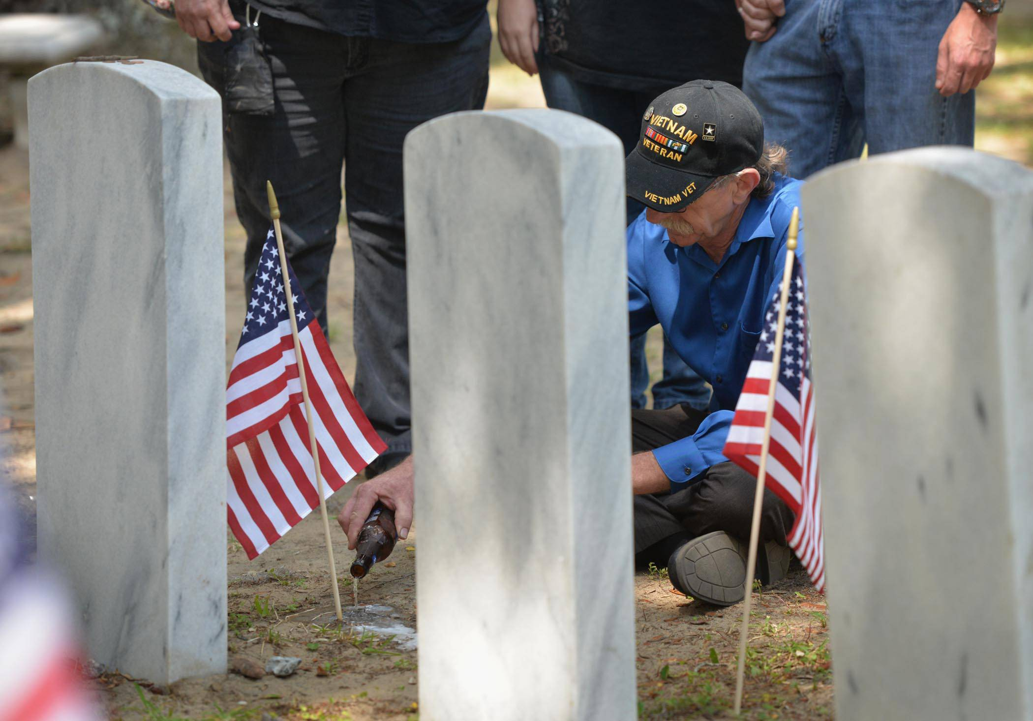 Vietnam veteran John Thomas Sansore of Bloomingdale, Ga., shares a beer with his friend Henry Allen Wheeler following the Memorial Day Ceremony in Bonaventure Cemetery in Savannah, Ga., Monday, May 26, 2014.