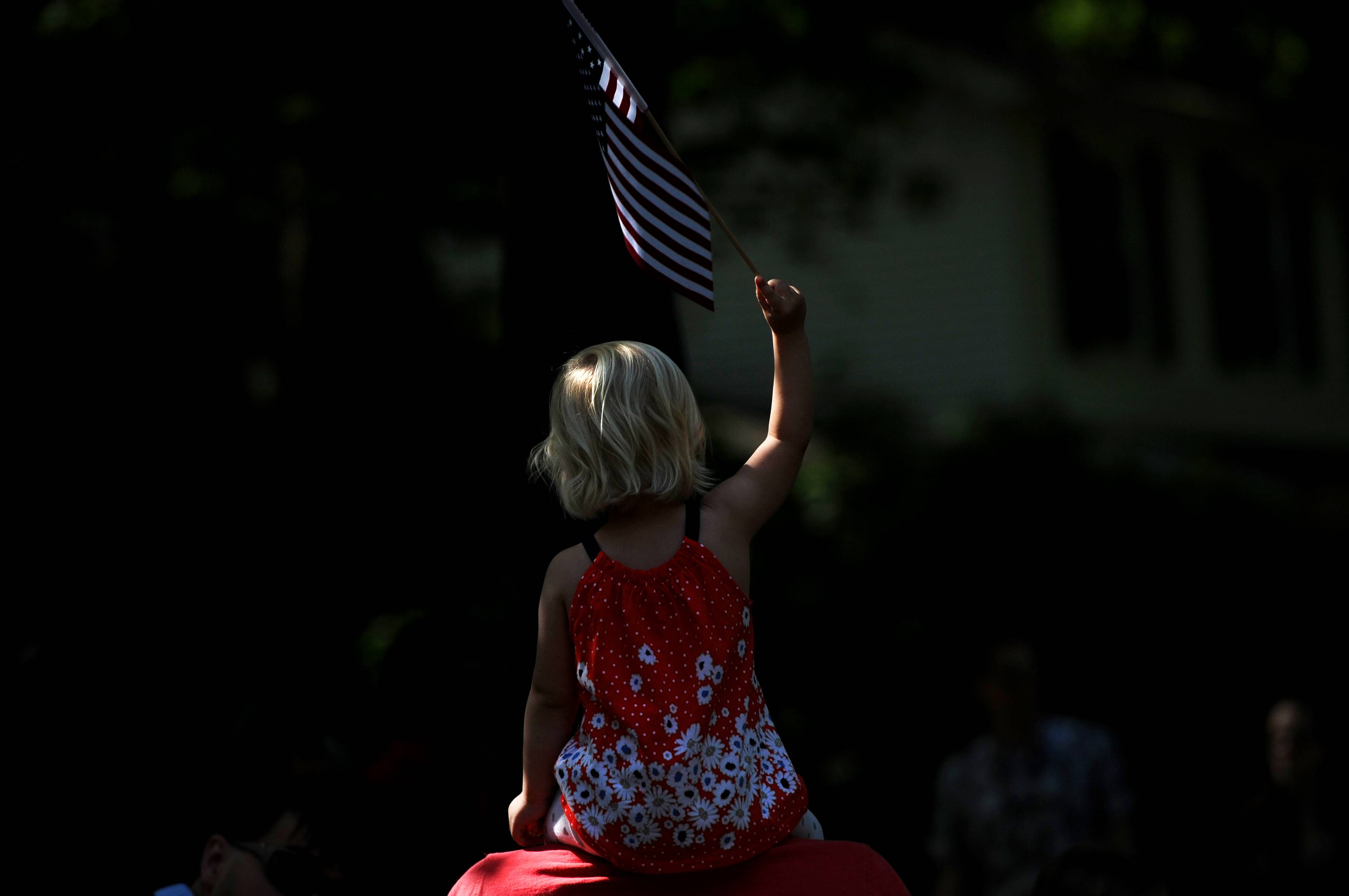 Emilia Thorsson, 2, waves an American flag as she sits on top of her father Thor's shoulders during the Glacier Highlands Memorial Day parade in the Glacier Highlands neighborhood in Ann Arbor, Mich., Monday, May 26, 2014.