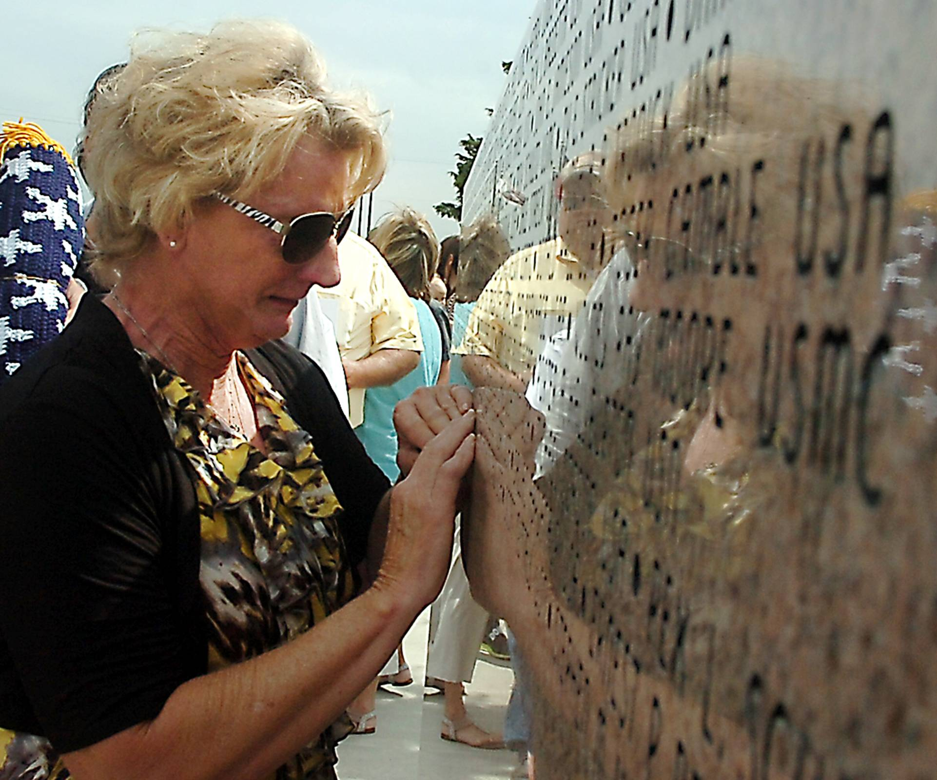 A woman touches the name of Capt. Shawn Walker on the Woodring Wall of Honor during Memorial Day ceremonies, Monday, May 26, 2014, in Enid, Okla.