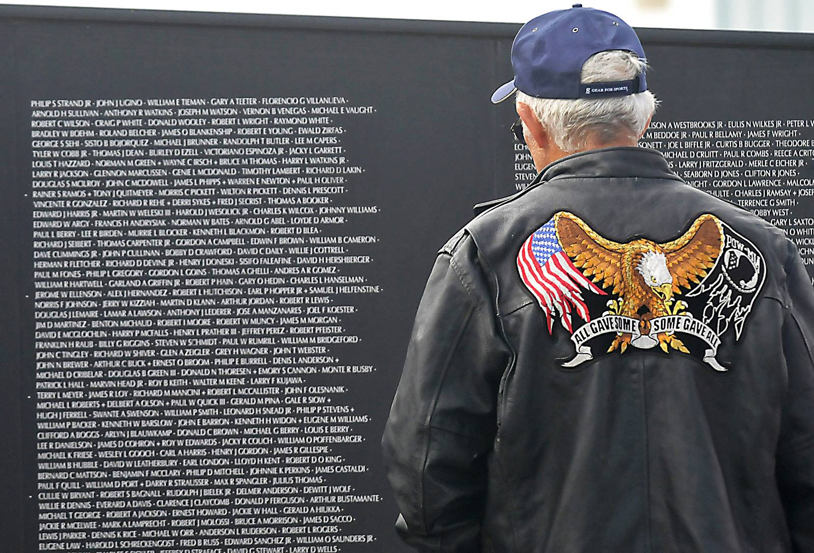 A veteran stares at the Vietnam Memorial Wall before the Woodring Wall of Honor Memorial Day ceremonies, Monday, May 26, 2014, in Enid, Okla.