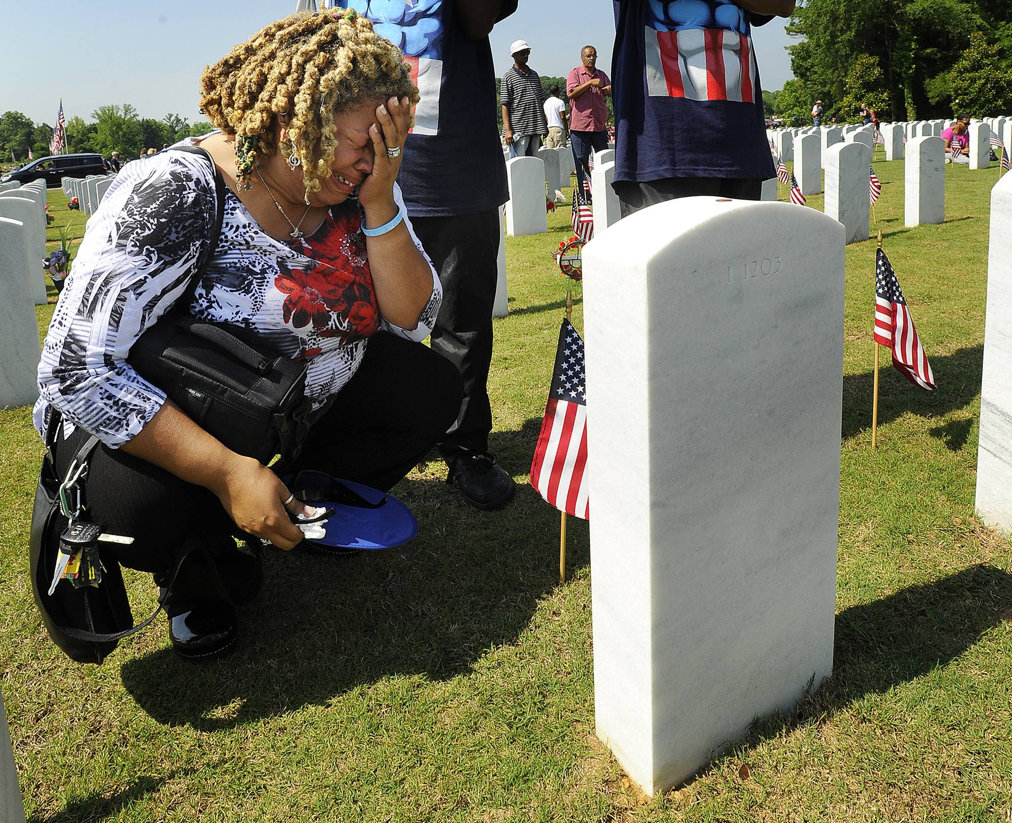 Victoria L. Coman-Jackson visits her husband's Dennis Wayne Jackson's grave after the annual Memorial Day Ceremony at the Alabama National Cemetery in Montevallo, Ala., Monday, May 26, 2014.