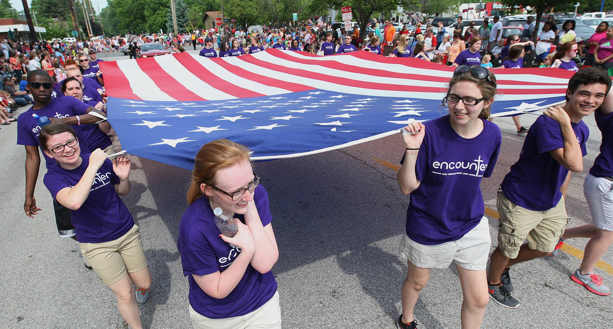 Members of the Christian music group called Encounter walk their large flag through the 147th annual Alton, Ill., Memorial Day Parade Monday, May 26, 2014. The Alton parade is believed to be the longest running consecutive Memorial Day Parade in the nation.