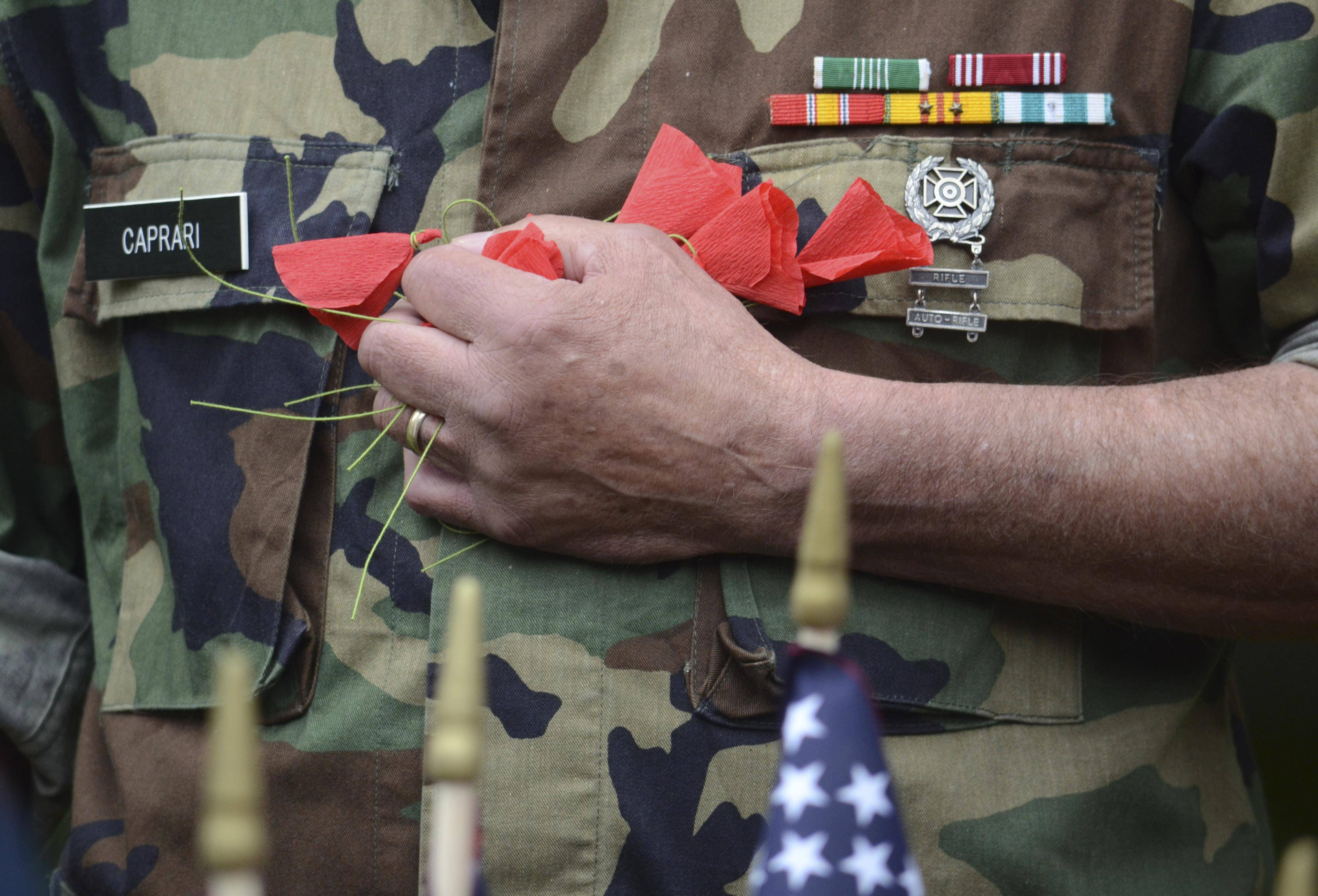 Larry Caprari, a veteran of the Vietnam War, holds poppies to be used to honor those who served in the military and died in service at a Memorial Day Ceremony at the Pittsfield, Mass., Cemetery, Monday May 26, 2014. As the names of those being remembered were read, a poppy was put in an urn to honor them.