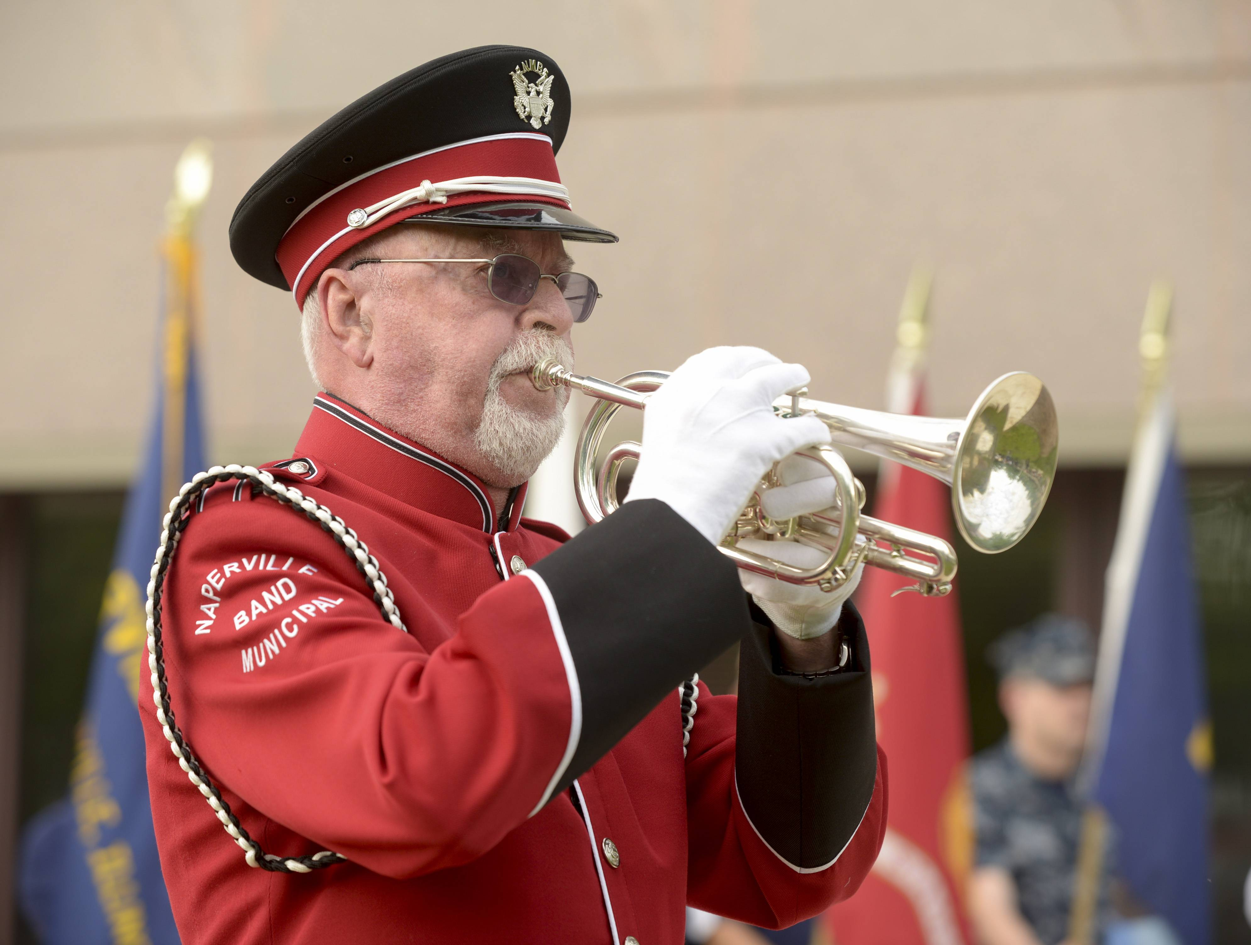 "Jerry Lahti, a Navy veteran and a member of the Naperville Municipal Band, plays ""Taps"" during the Naperville Memorial Day service."