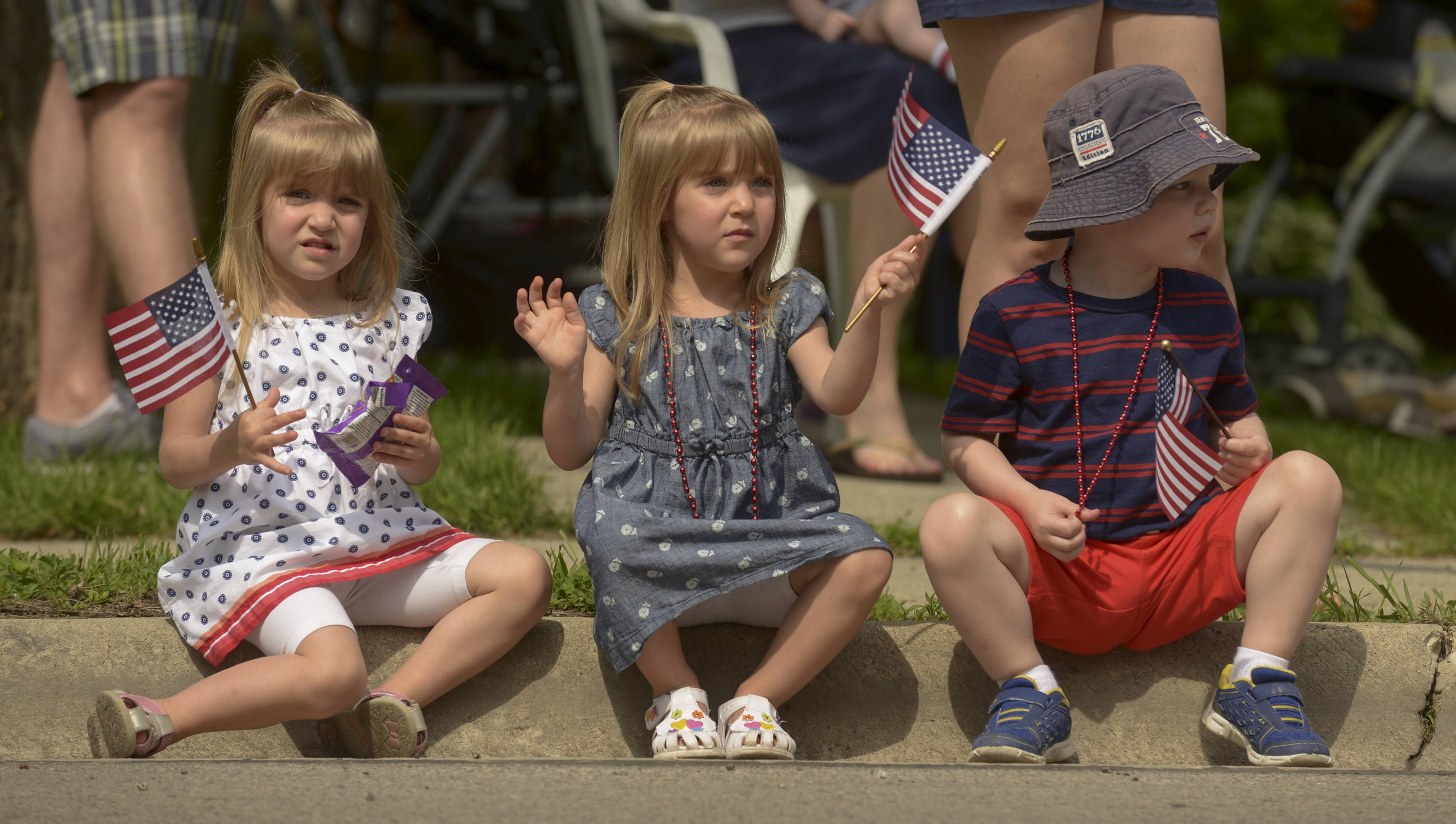 Olivia and Avery Pecak, 3 of Lisle along with Graem Wiegand, 3 of Wheaton waves their American flags during the Wheaton's Memorial Day parade.