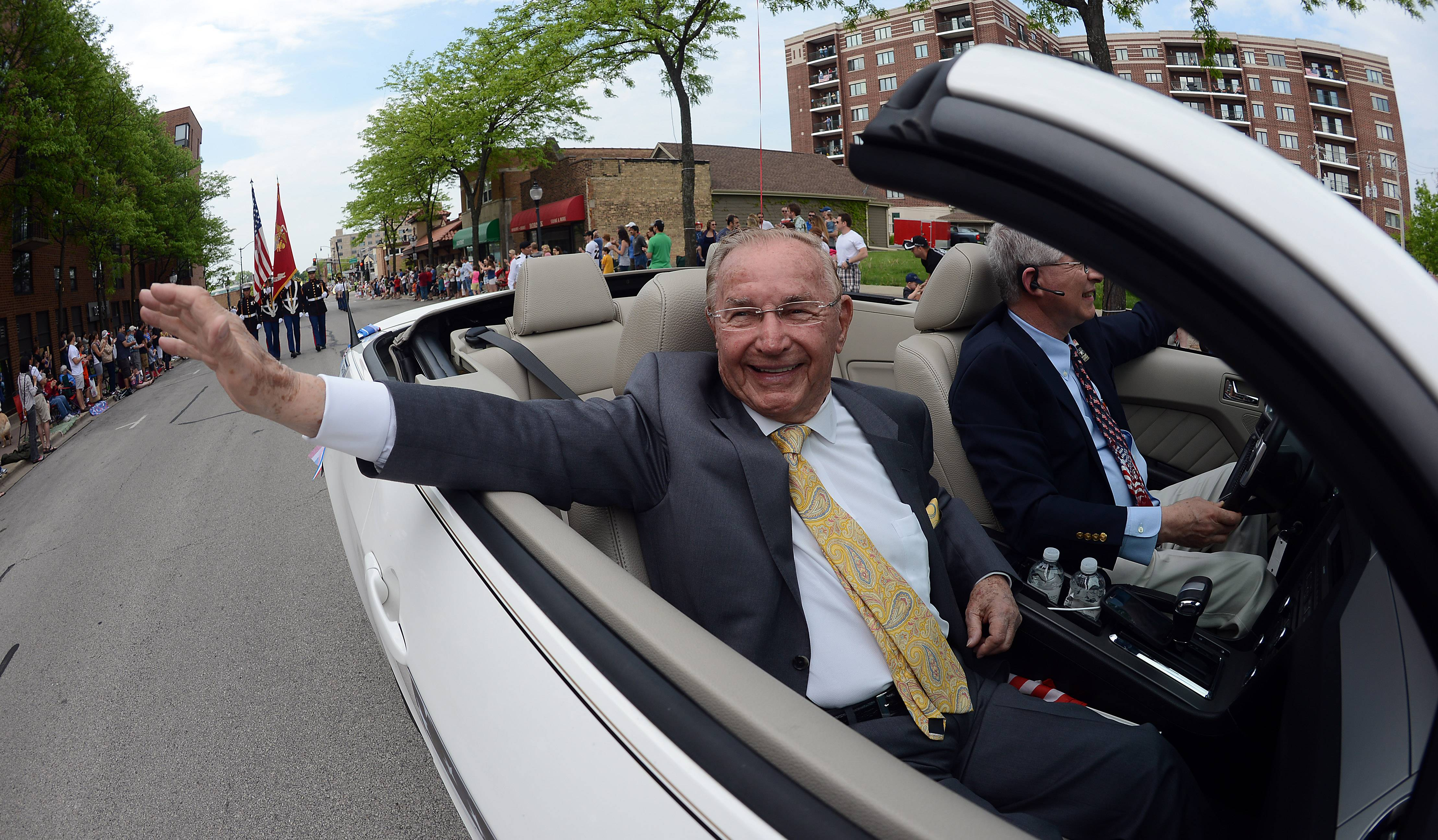 Richard Duchossois, grand marshall of the parade and World War II veteran waves to the people during the parade route in Arlington Heights on Memorial Day Monday.