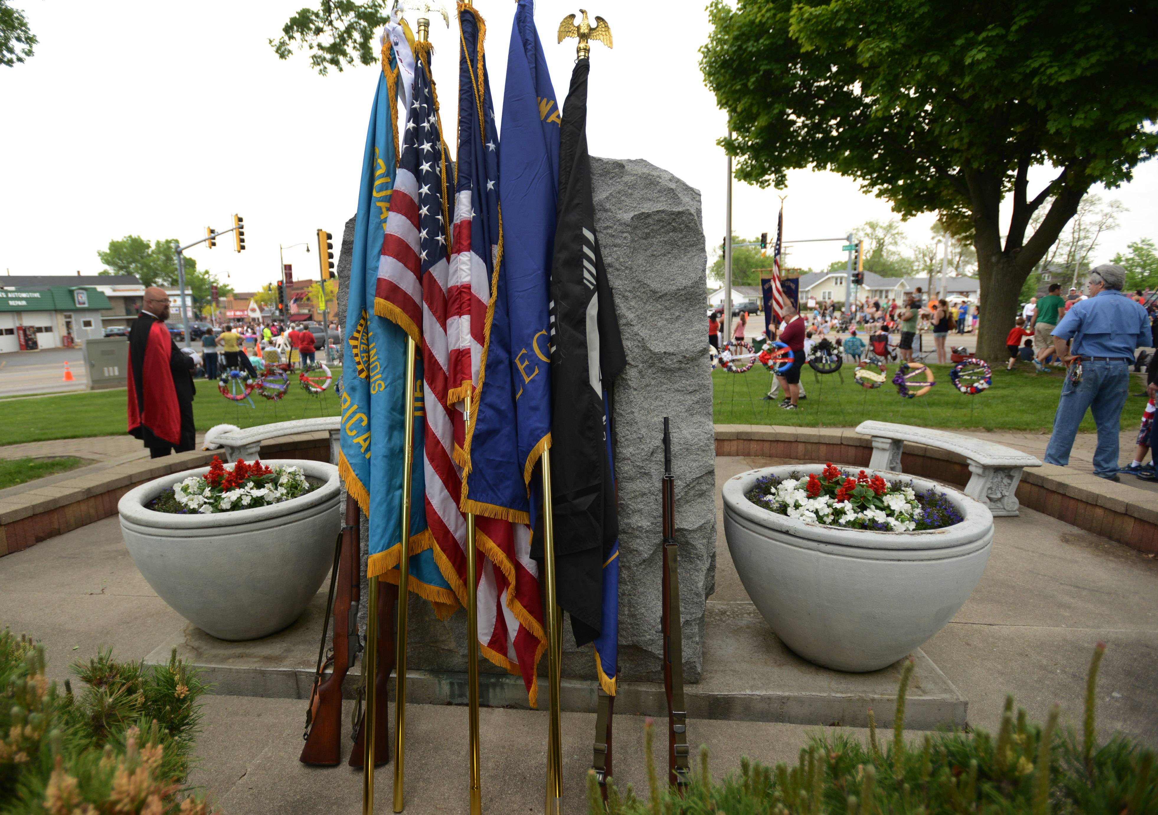Flags and rifles rest on a memorial in Wauconda Monday as officials wait for the parade to finish before starting the Memorial Day ceremony.